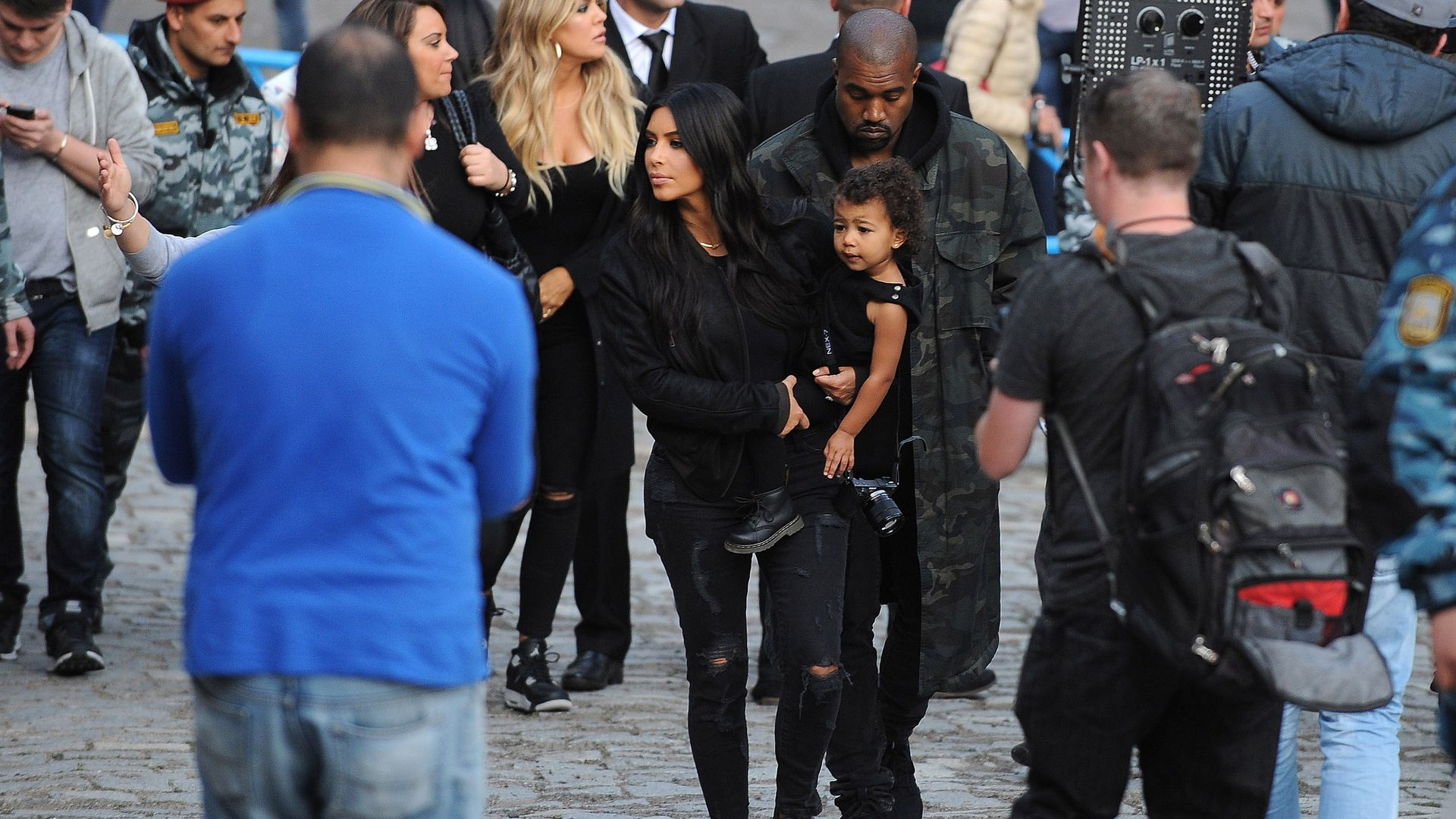 Kim Kardashian carrying her child with Kanye West behind her