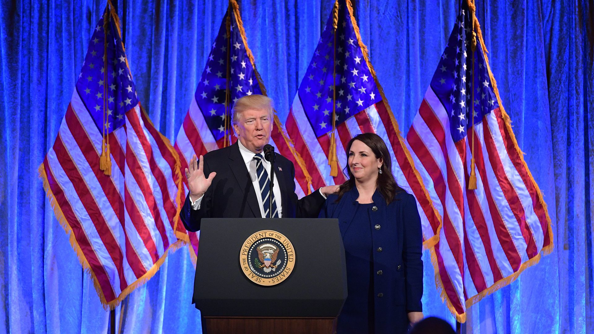 President Trump and RNC Chairwoman Ronna McDaniel in front of a blue curtain and a line of American flags.