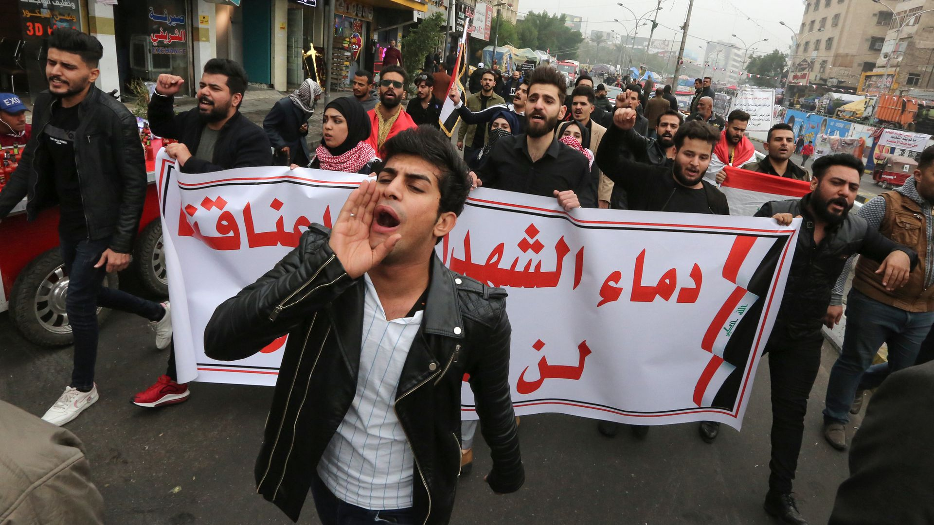 "Iraqi protesters carry a banner which reads ""The blood of martyrs is entrusted to us, it will not be in vain"" during a march in Tahrir Square"