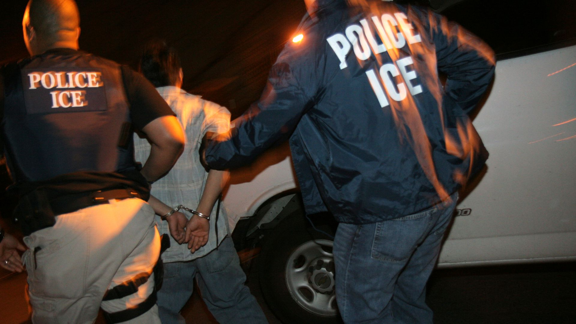 ICE agents detain someone.