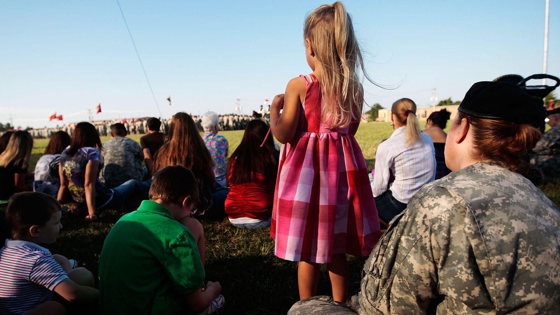 A little girl stands and watches a deployment ceremony.