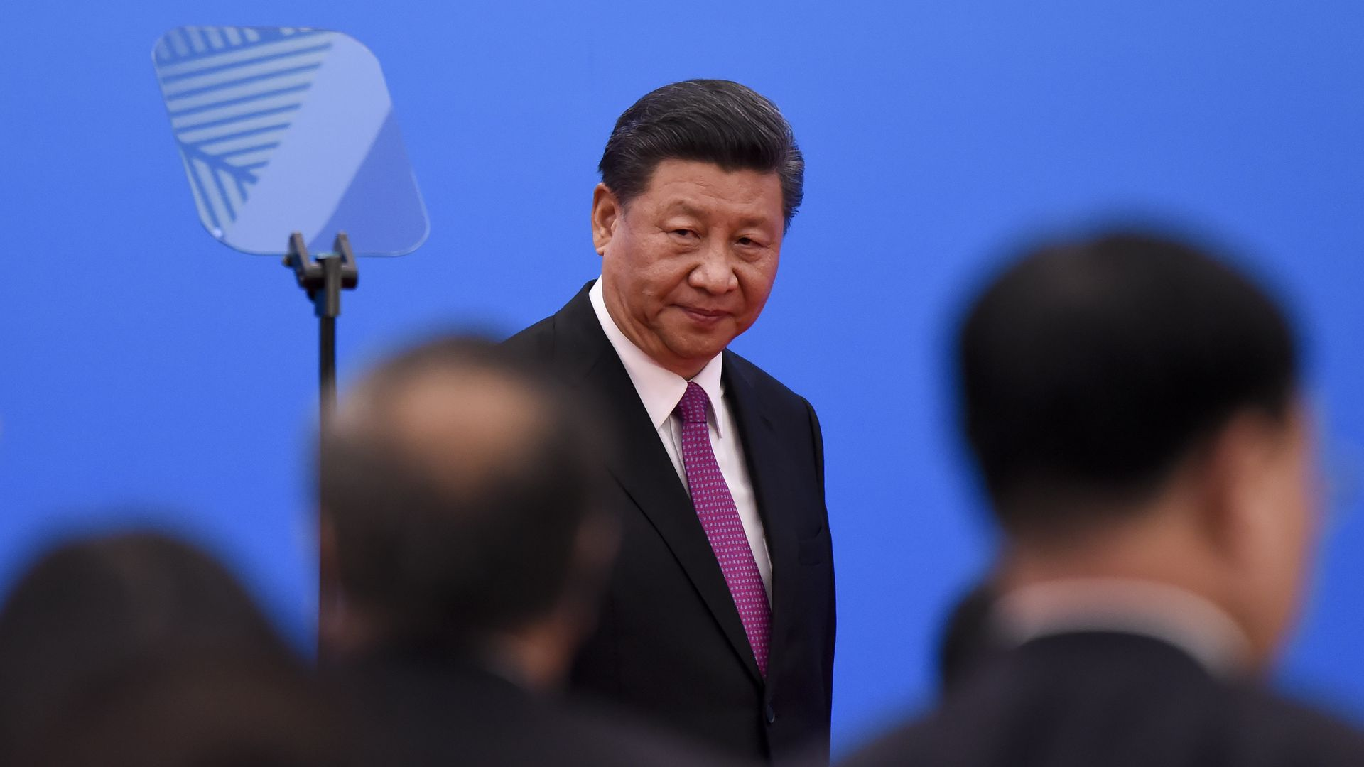 In this image, Xi Jinping looks to the left while walking on a stage.