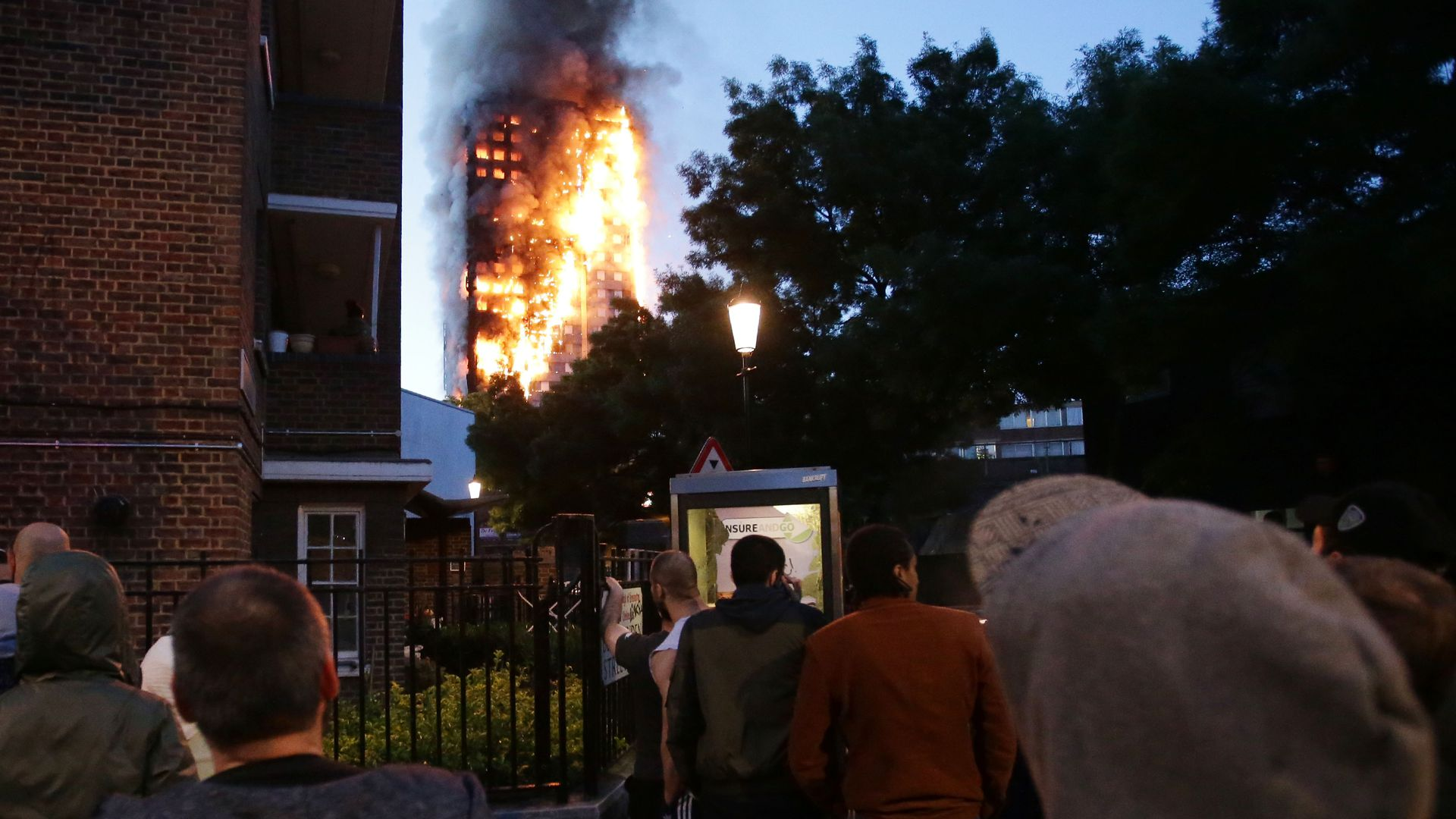 Local residents watch as Grenfell Tower is engulfed by fire on June 14, 2017 in west London.