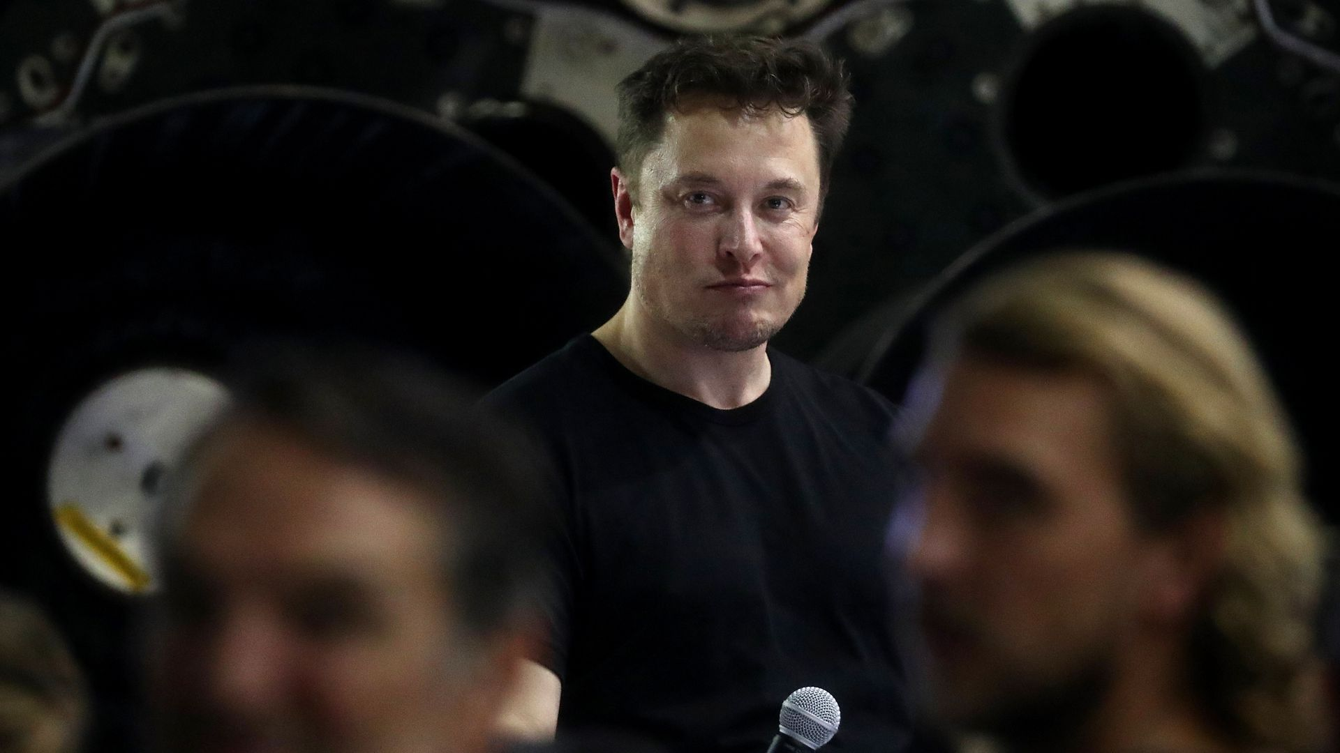 Elon Musk holds a microphone in a crowd.