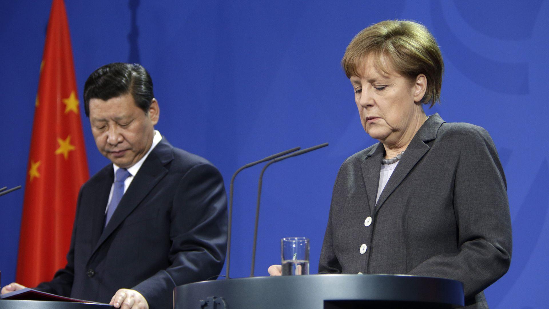 Xi and Merkel both look down