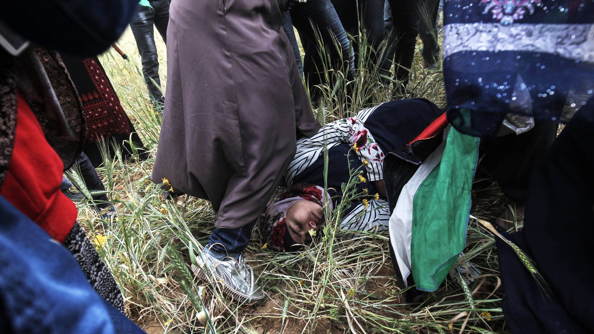 Injured Palestinian woman laying on the ground