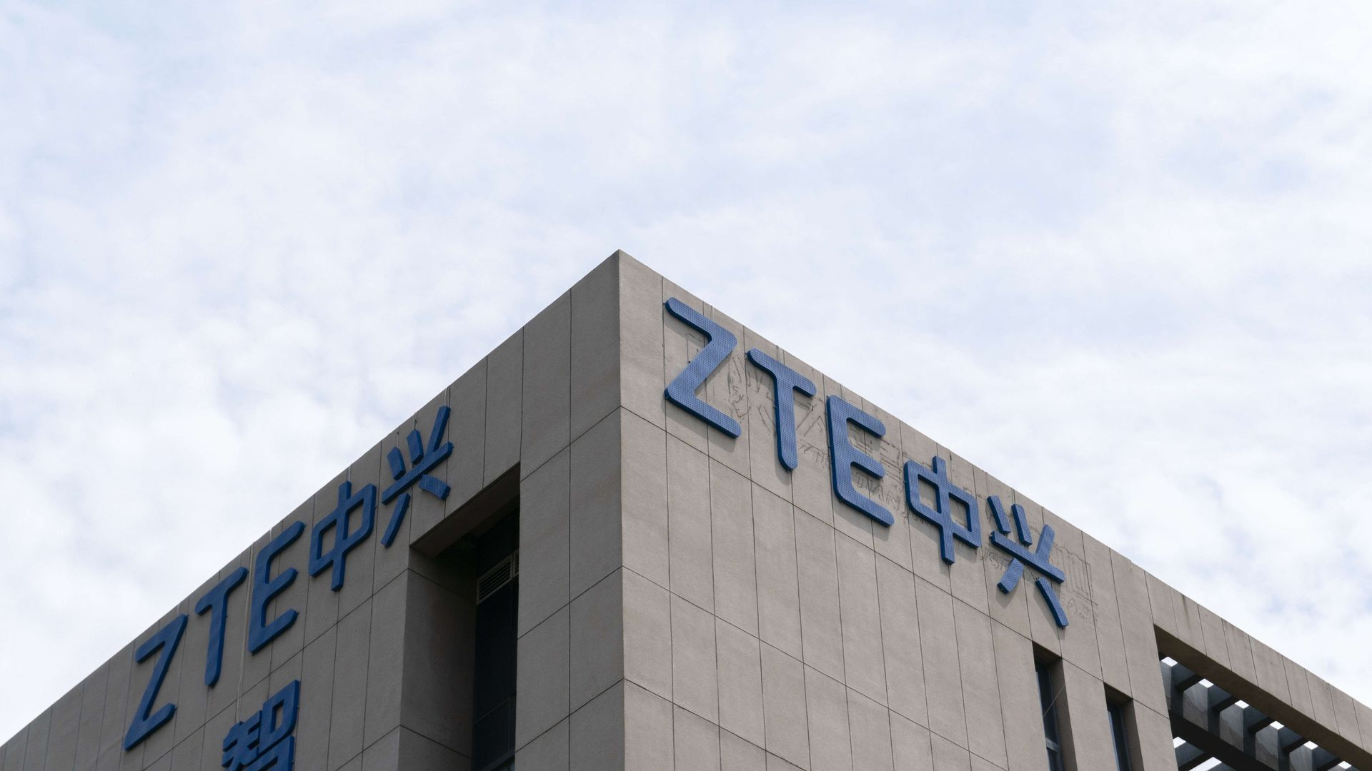 Corner of a building with ZTE logo against blue sky