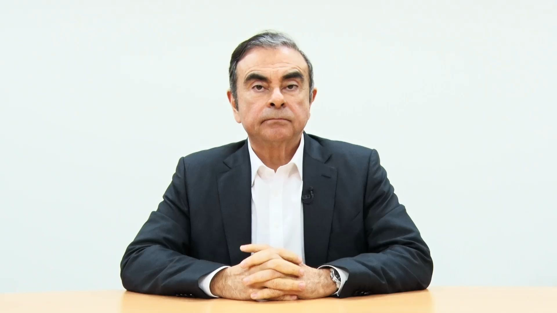 Carlos Ghosn sitting at a table with his hands crossed.