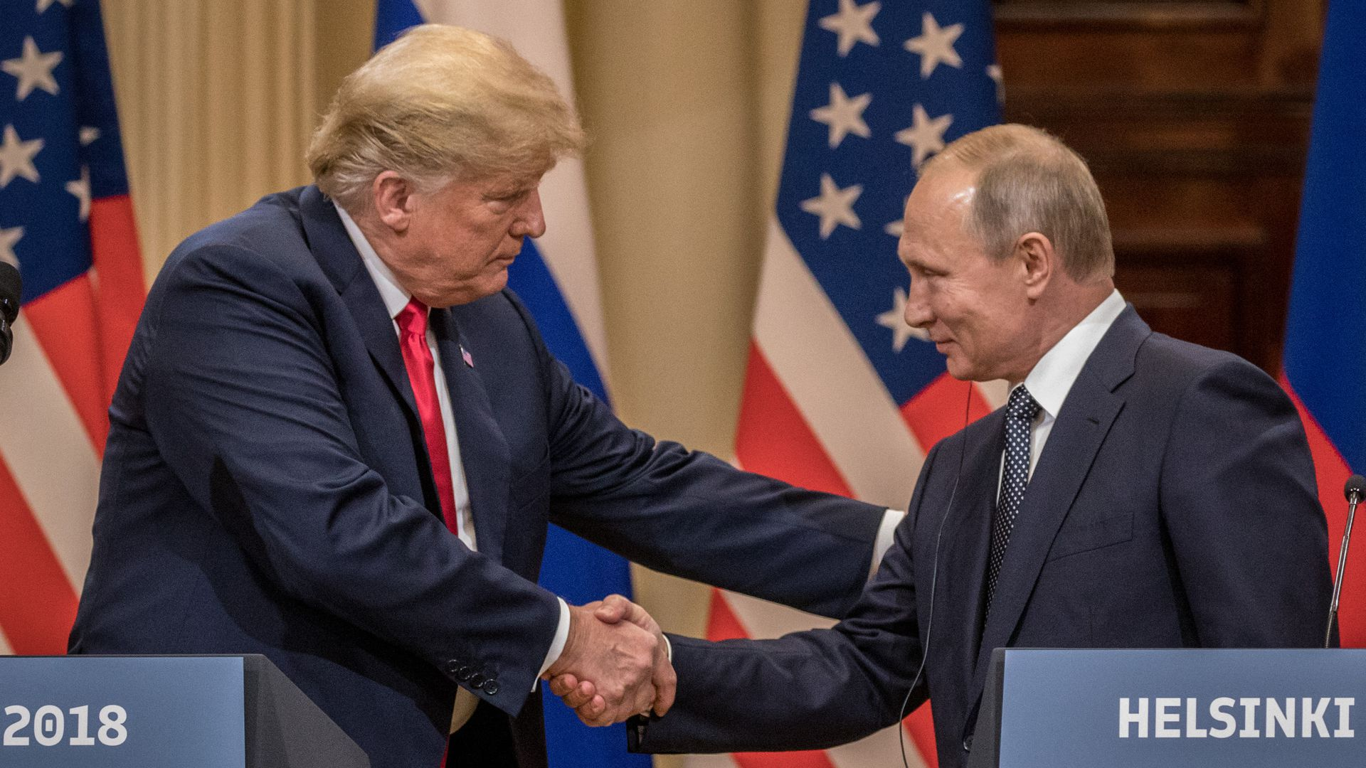 Trump and Putin smile and shake hands behind podiums in Helsinki