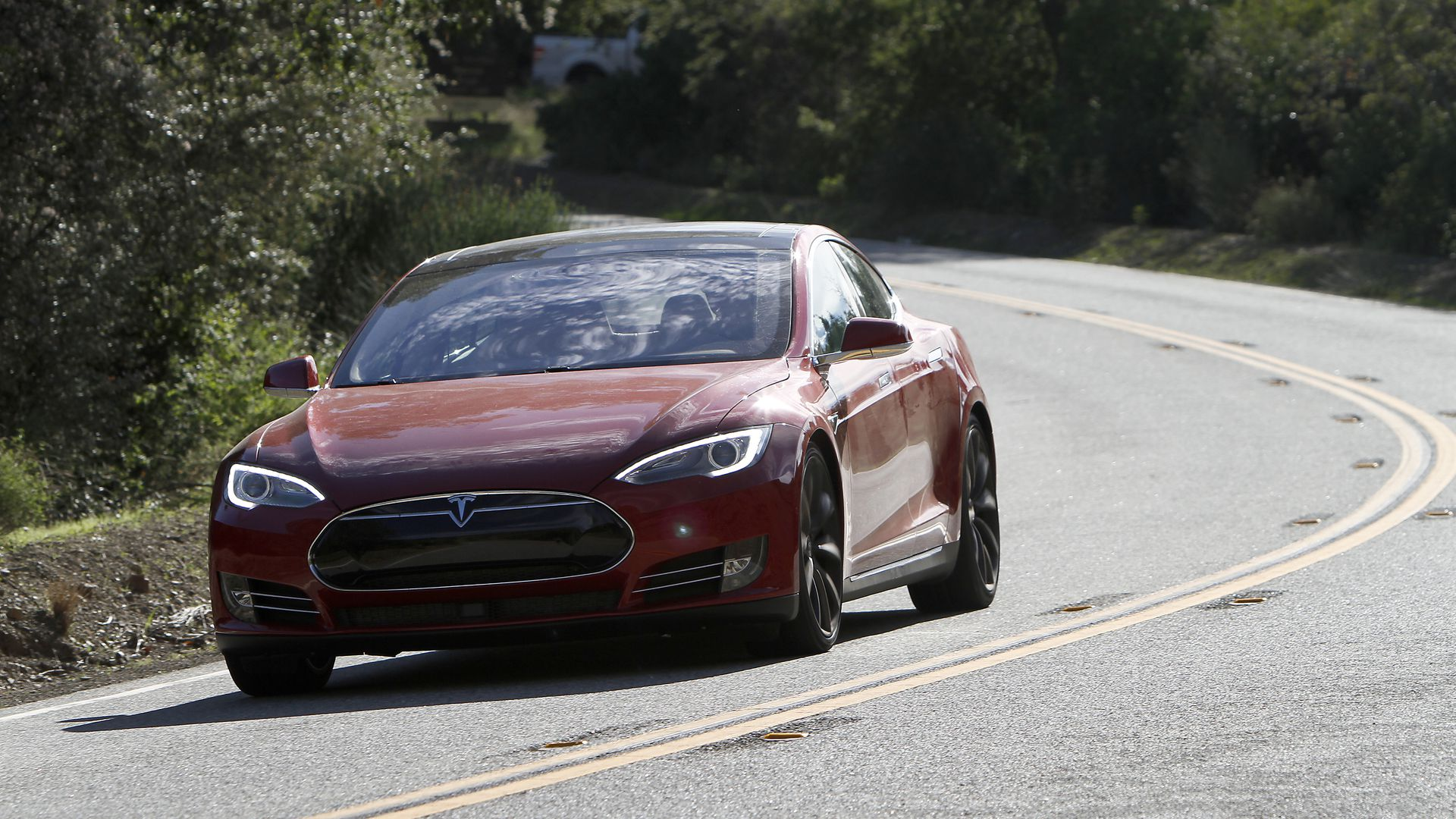 Red Tesla Sedan driving on the road.