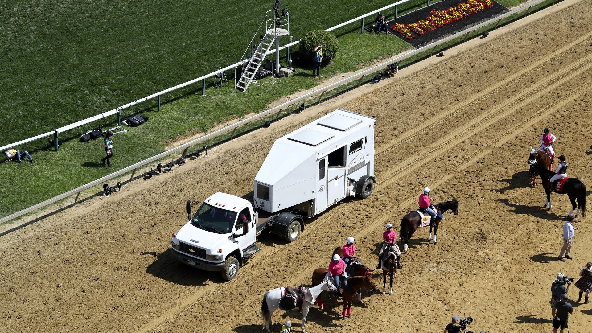 A horse ambulance retrieves a horse body from the race course