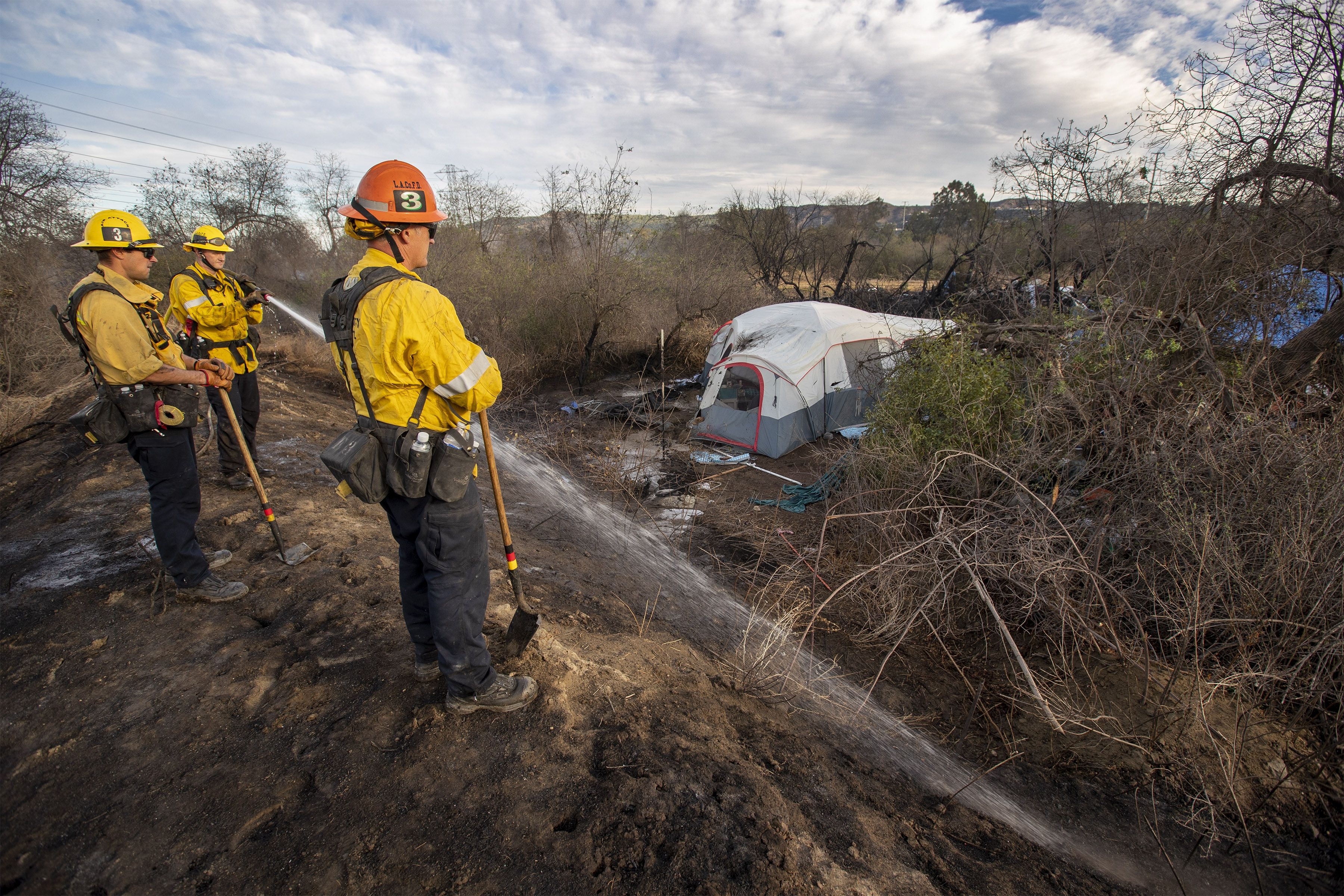 Los Angeles County Fire Dept. firefighters put out a hot spot in the Durfee Fire that spread to a homeless encampment in the Whittier Narrows Recreation Area in South El Monte, on Tuesday, Dec. 8