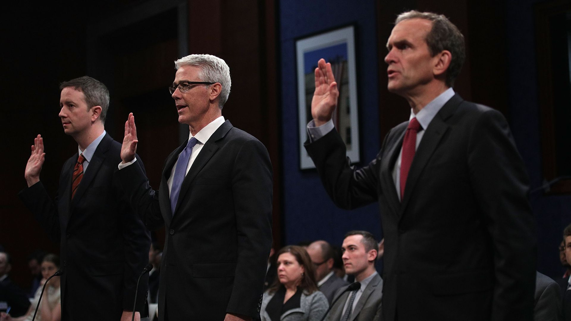 Witnesses from major tech companies raise their right ends to be sworn in before Congress