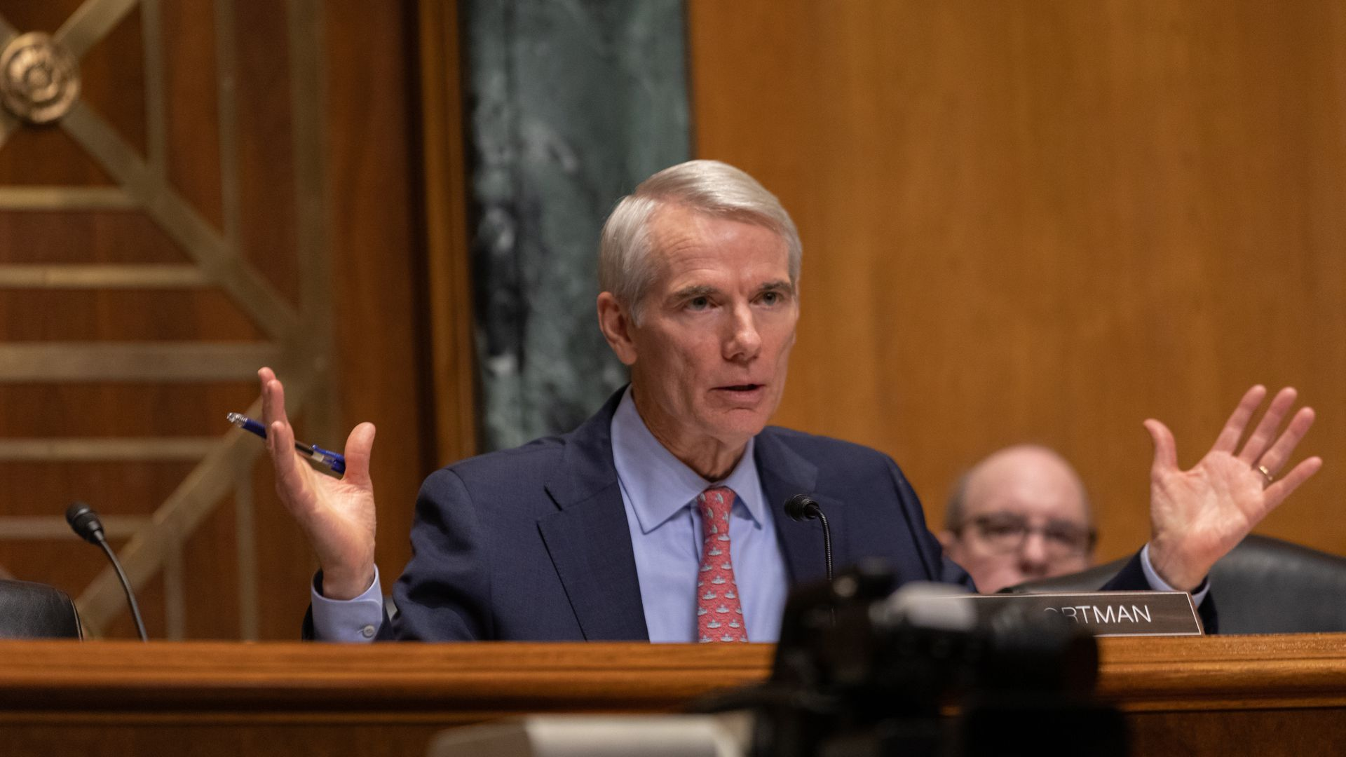 Rob Portman sits at a dais with his nameplate in front of it.