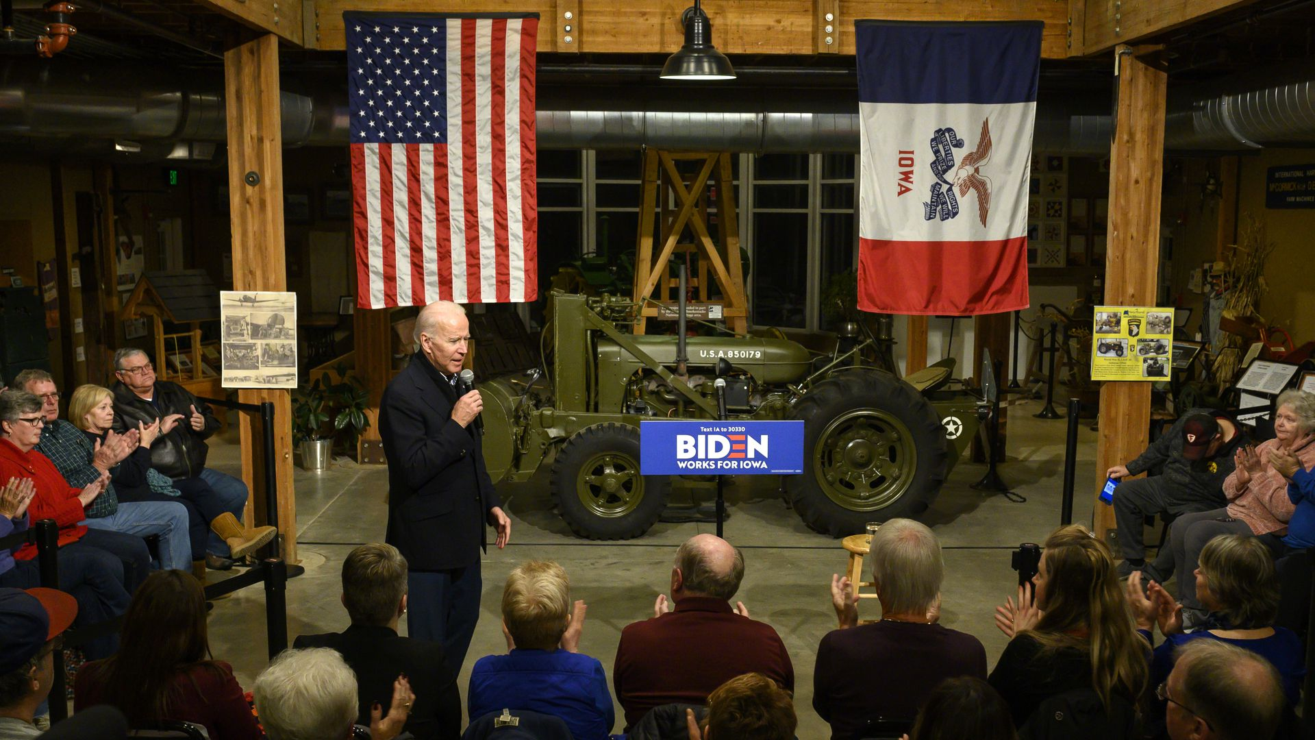 Biden addresses a crowd on a stage with an American flag and Iowa flag in the background