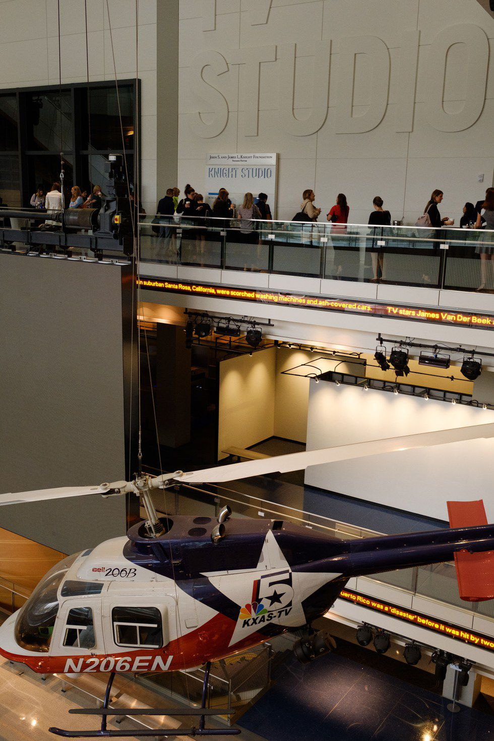 Guests on a balcony above a helicopter in a museum
