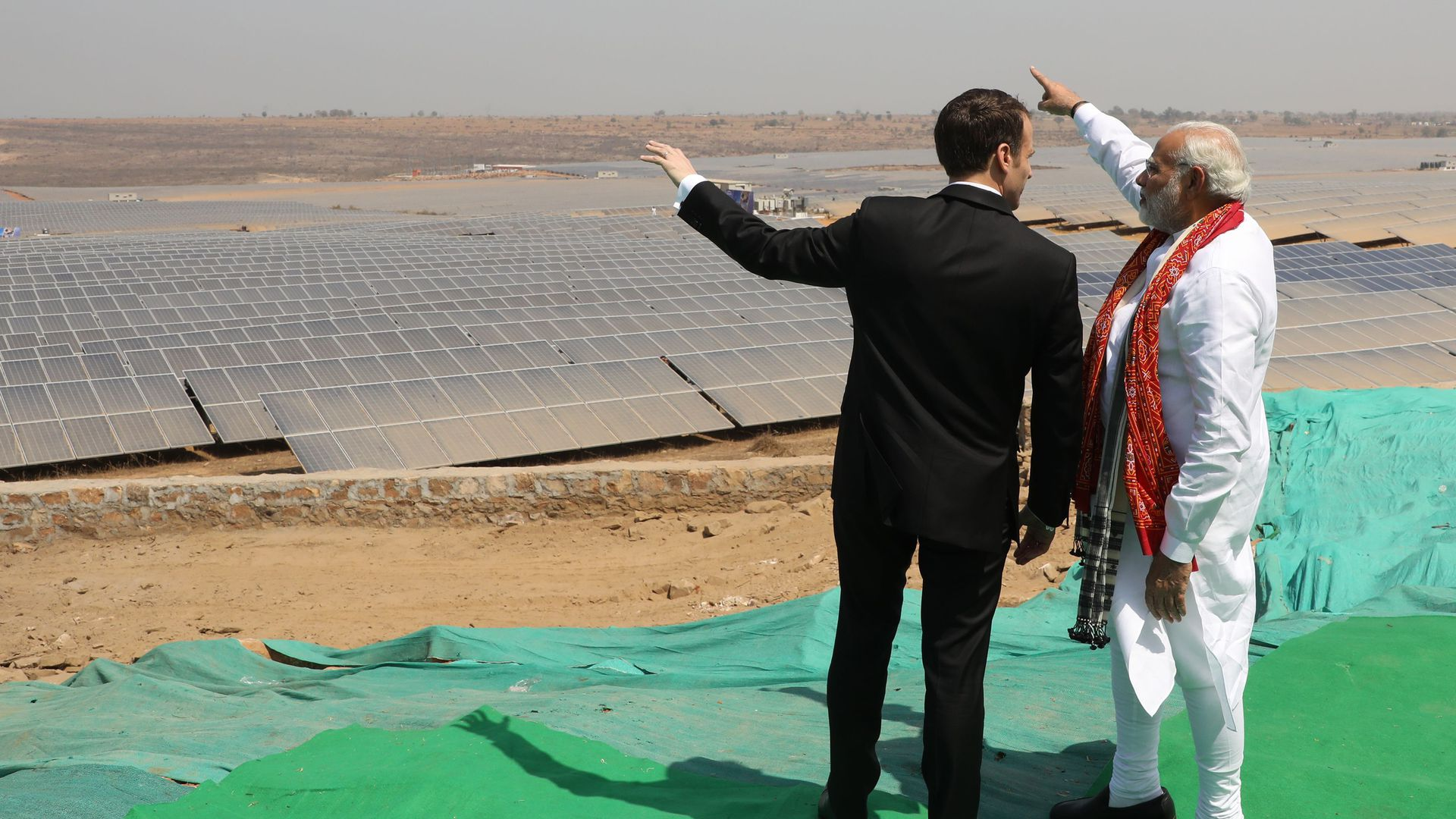 Indian Prime Minister Narendra Modi and French President Emmanuel Macron stand together during the inauguration of a solar power plant in Mirzapur in Uttar Pradesh state on March 12, 2018.