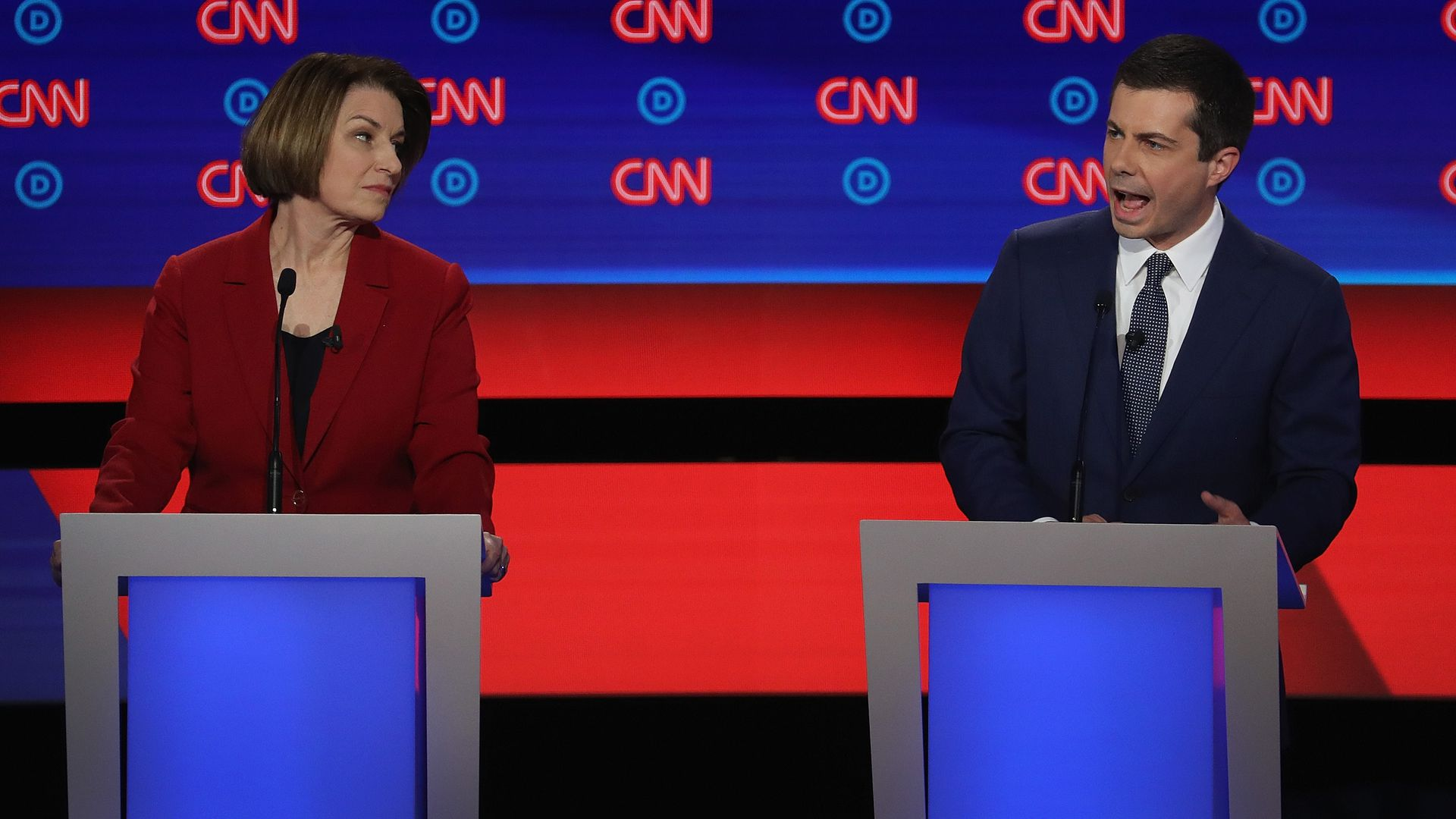 In this image, Klobuchar and Pete Buttigieg speak behind two different podiums on stage with the CNN logo behind them.