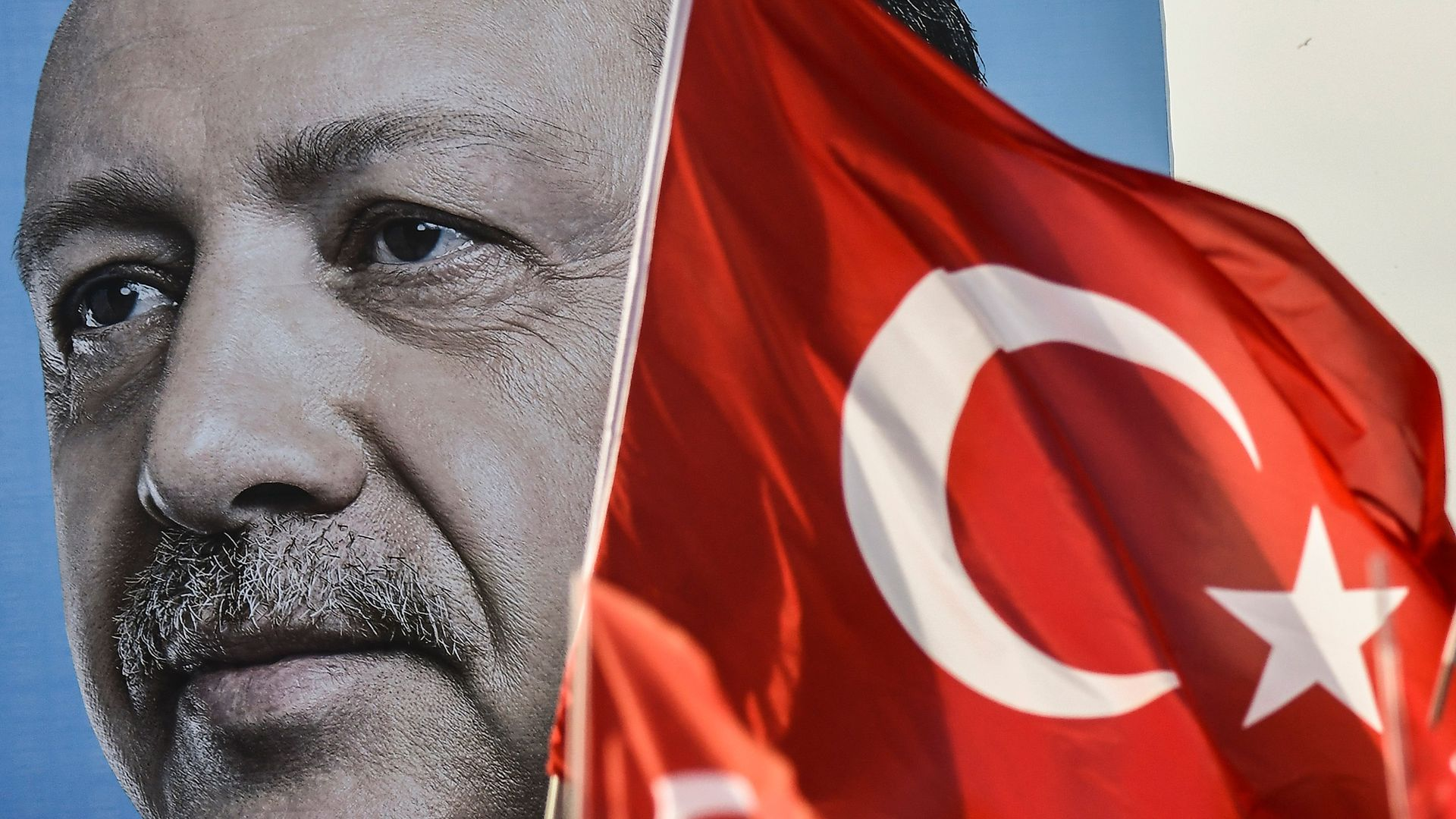A giant campaign poster of Turkey's President Erdogan next to a Turkish flag.