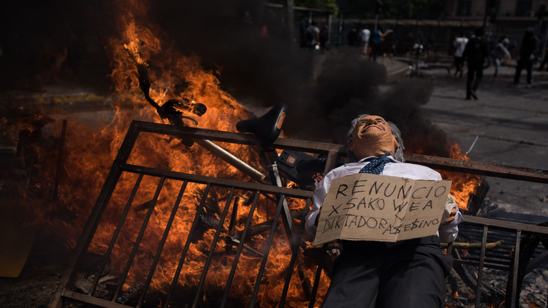 Protesters burn barricades as they gather to march on the sixth day of social riots for increases in public transport in Santiago of Chile.