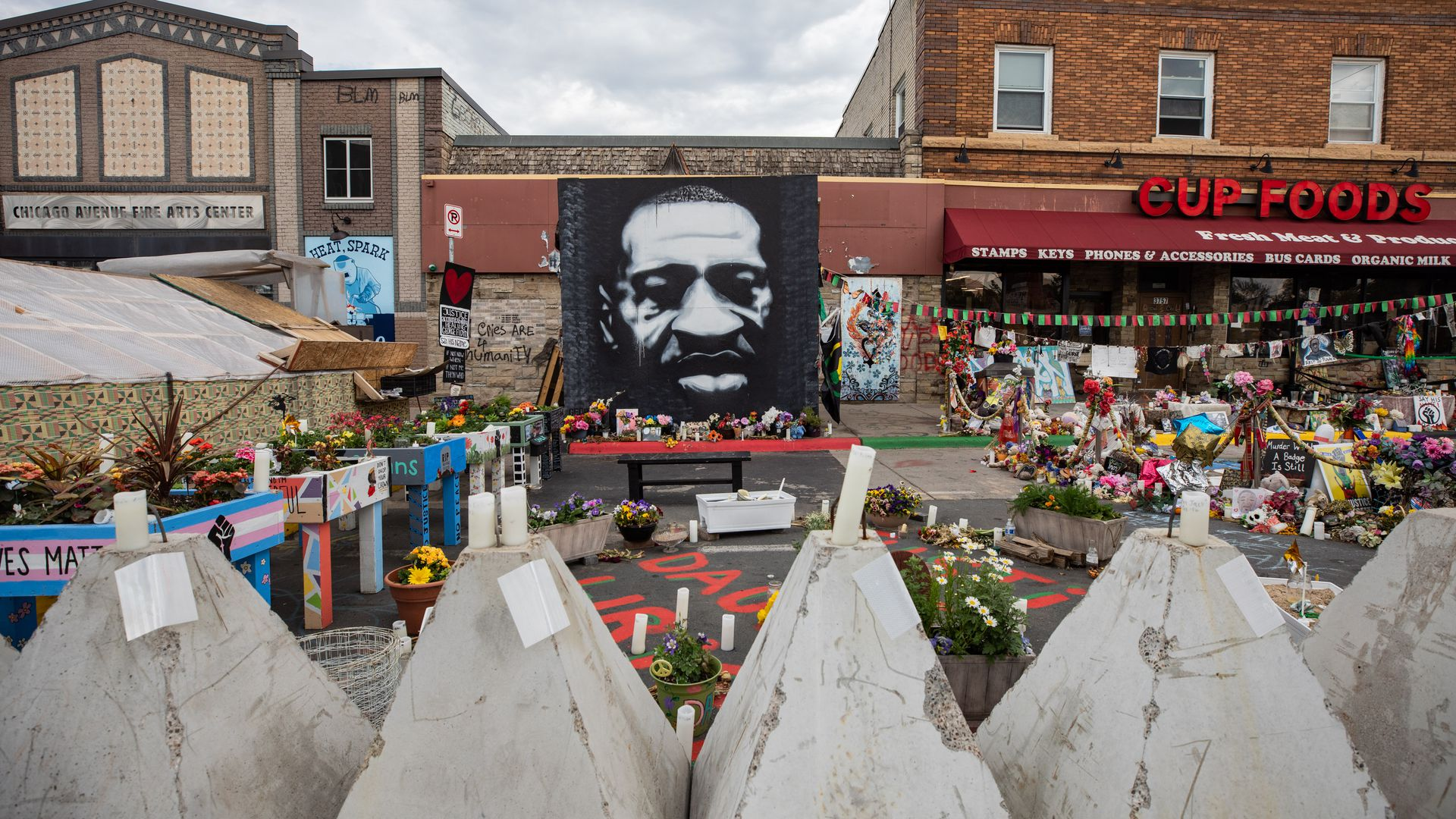 Photo of a memorial site outside a Cup Foods store, with a large portrait of George Floyd propped up in the center