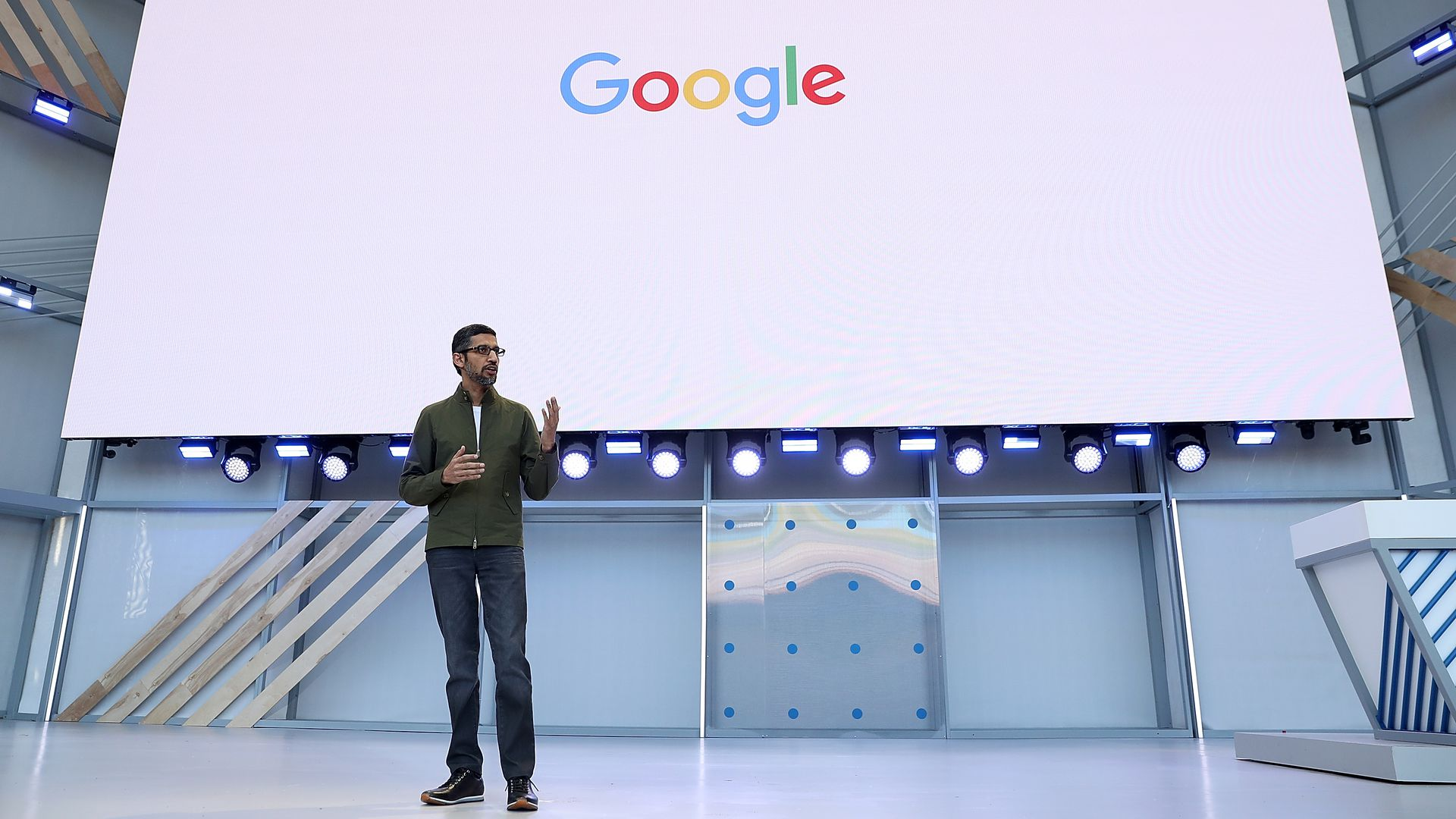 Google logo on a white screen above Sundar Pichai talking with hands up
