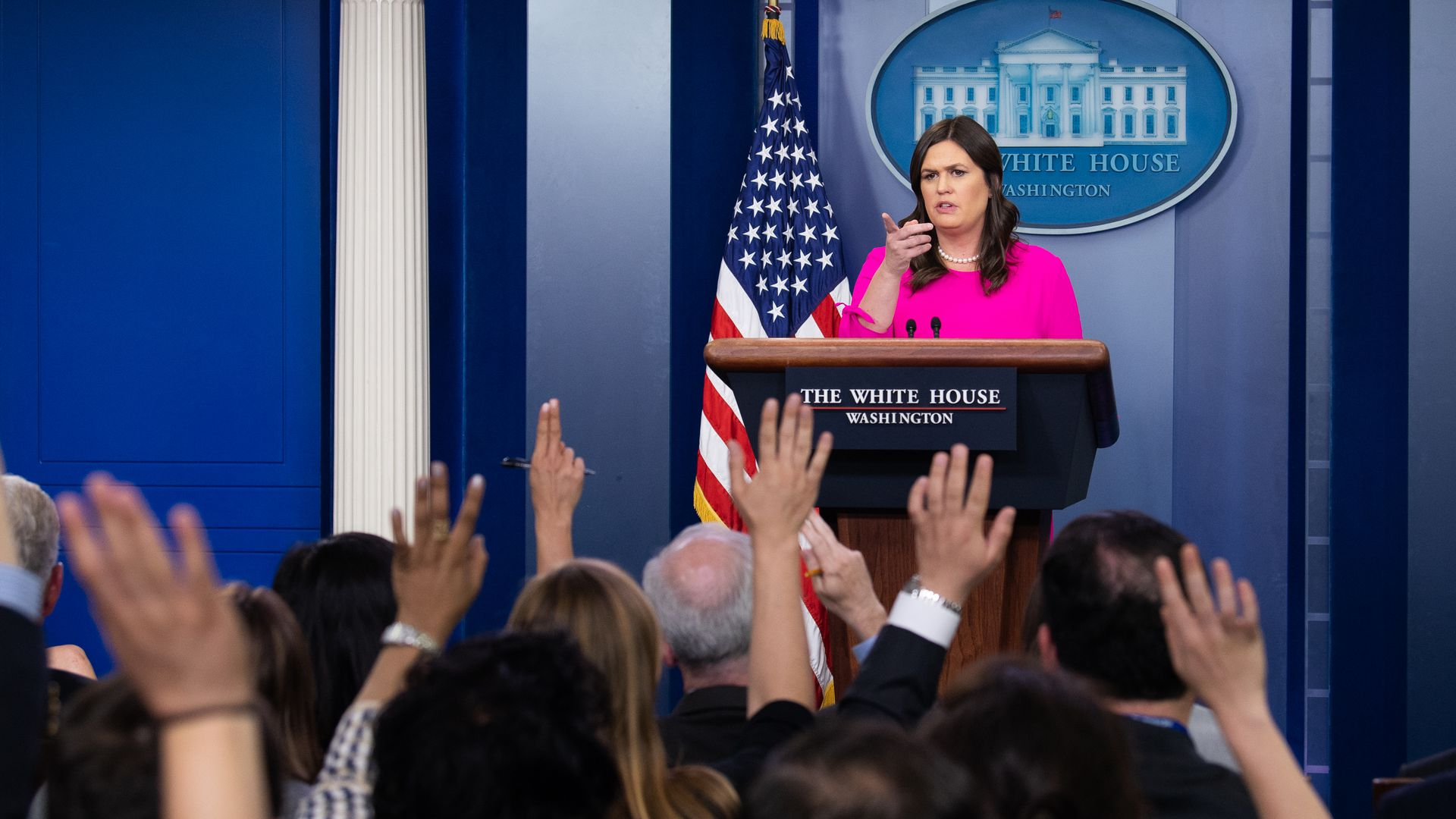 Sarah Sanders in a pink jacket a the White House briefing room stand