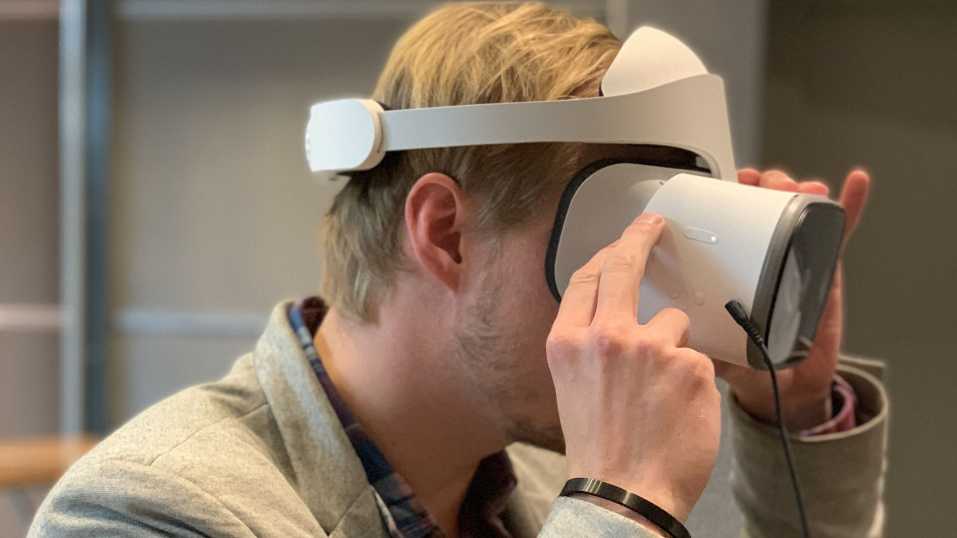 A seated man wearing a virtual reality headset