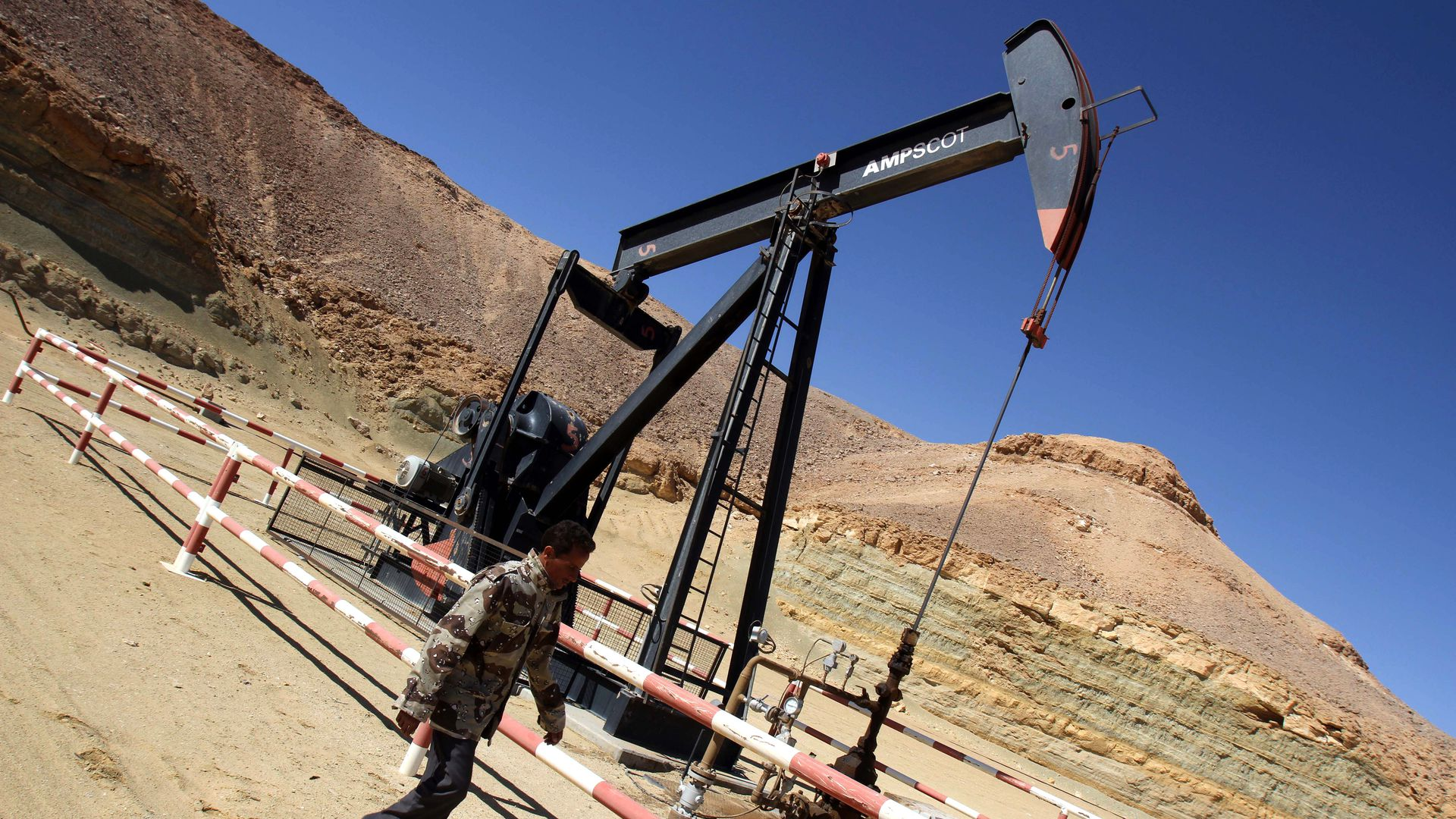 A Libyan security member walks by an oil drill.