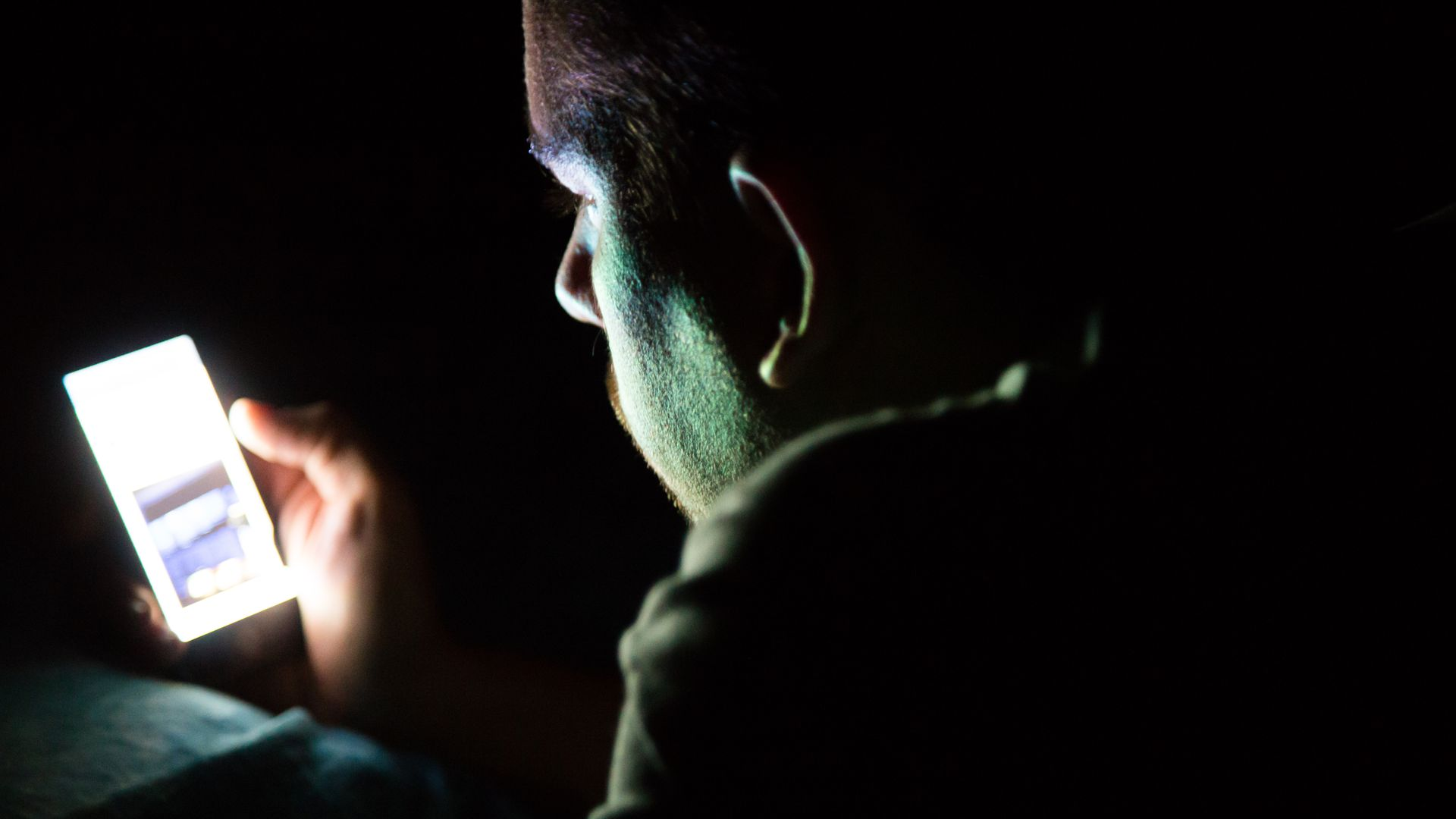 A mani in the dark looks at a smartphone, which illuminates his face