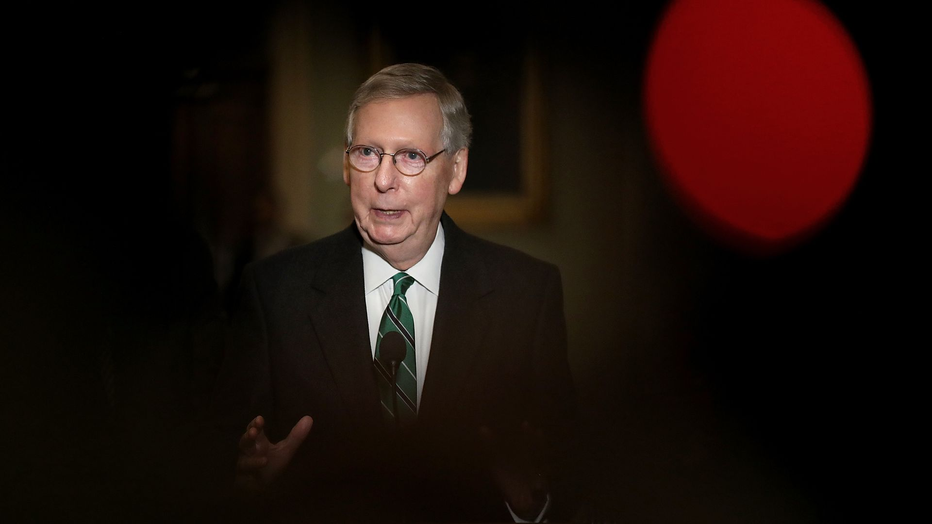 Mitch McConnell stand in a spotlight surrounded by darkness