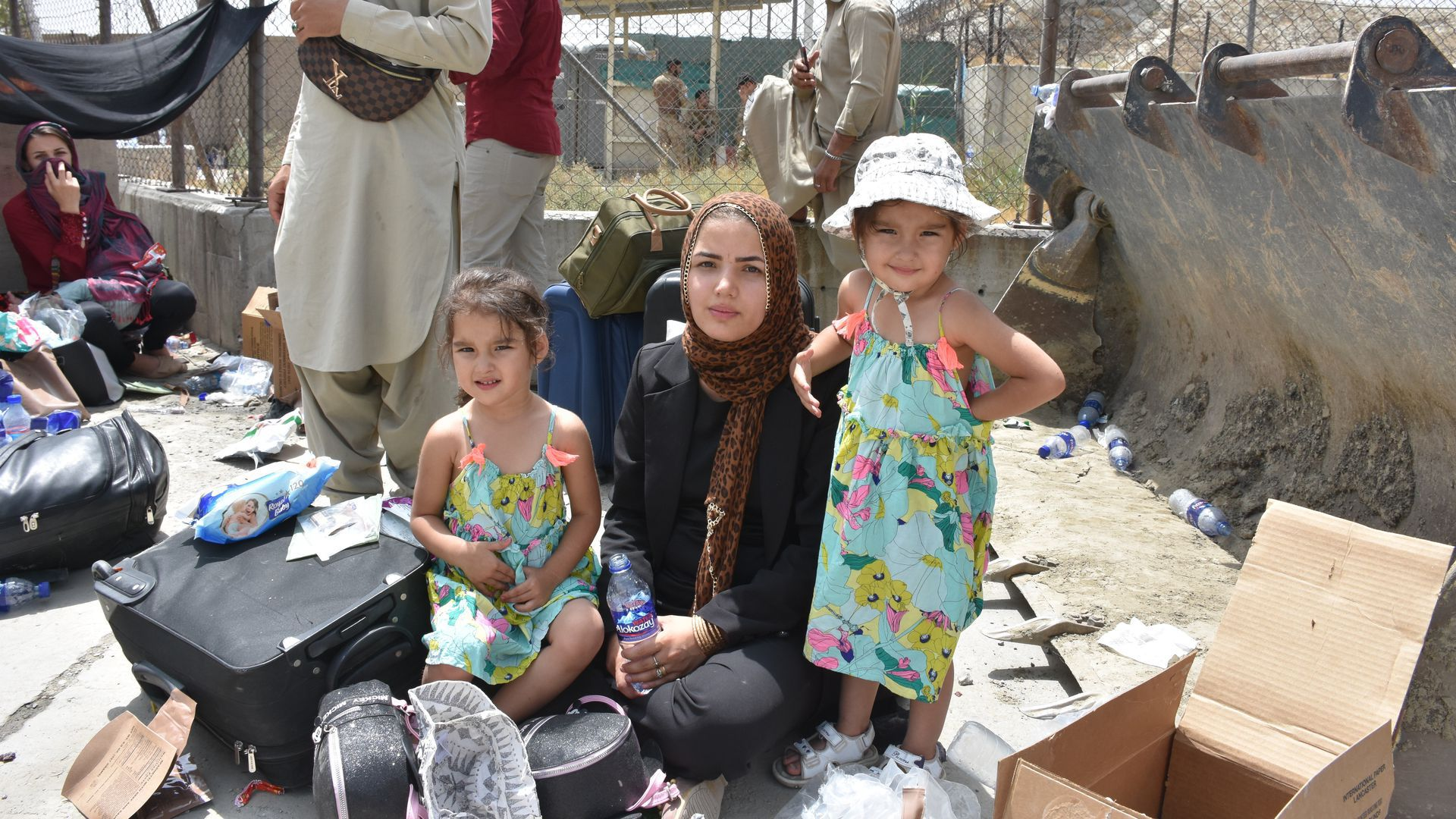 A photo of Afghan refugees -- a mother and her two daughters -- sitting alongside their belongings