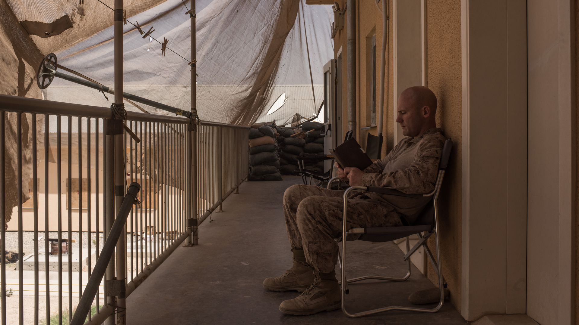 A U.S. marine reads a book sitting in a chair.