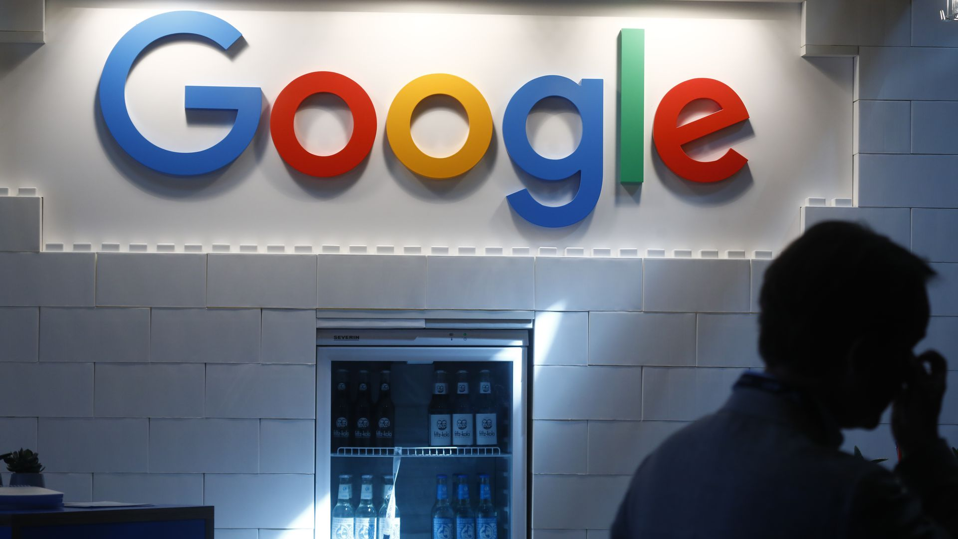 Google sign against a cinderblock wall over a refrigerator