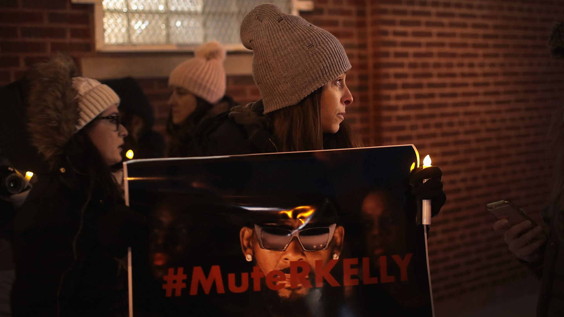 "In this image, a woman in a winter coat and gloves holds a sign that says ""Mute Kelly."" The words on the sign are written in red over a picture of R. Kelly's face."