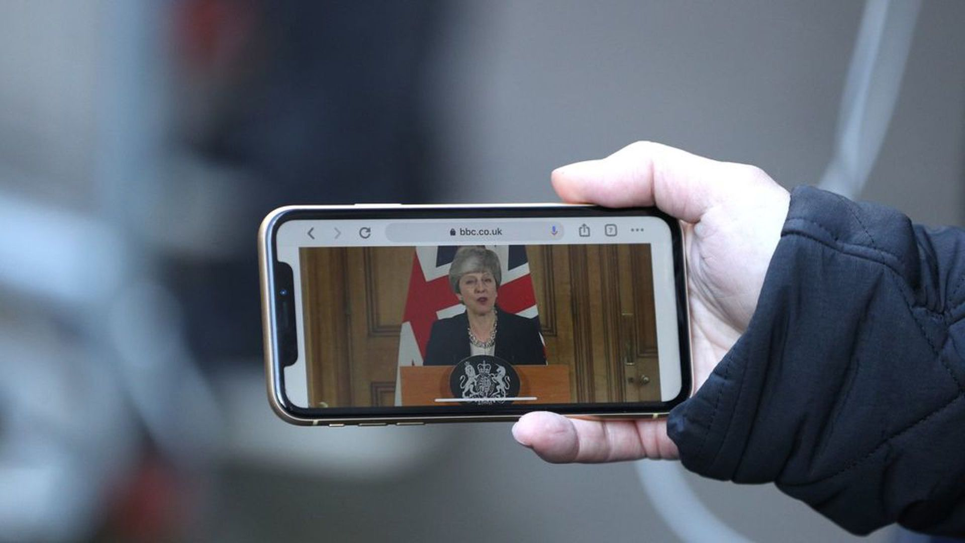 Theresa May speaking at a press conference. Someone streams it on their phone
