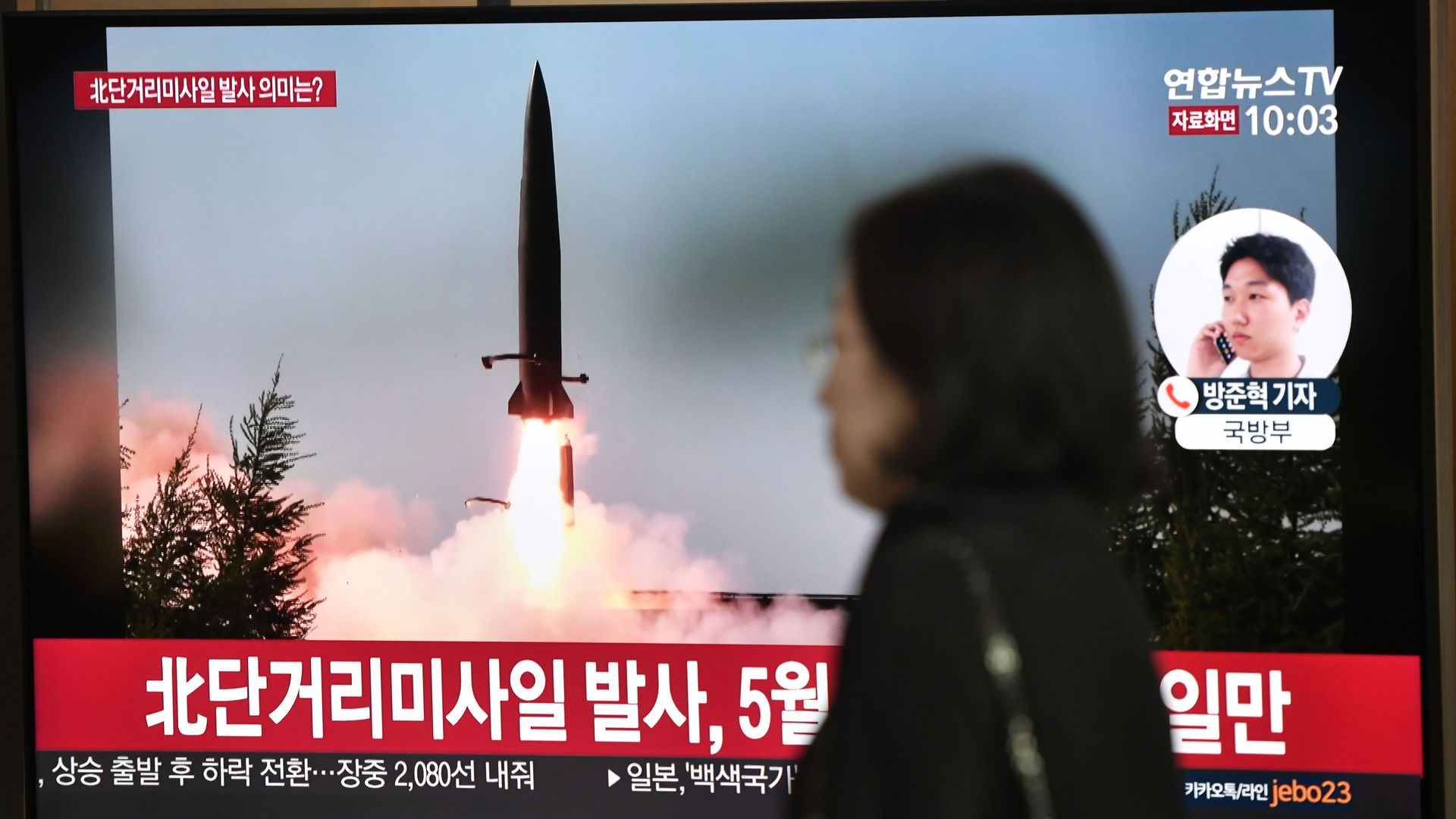 woman standing next to a television showing a missile launch