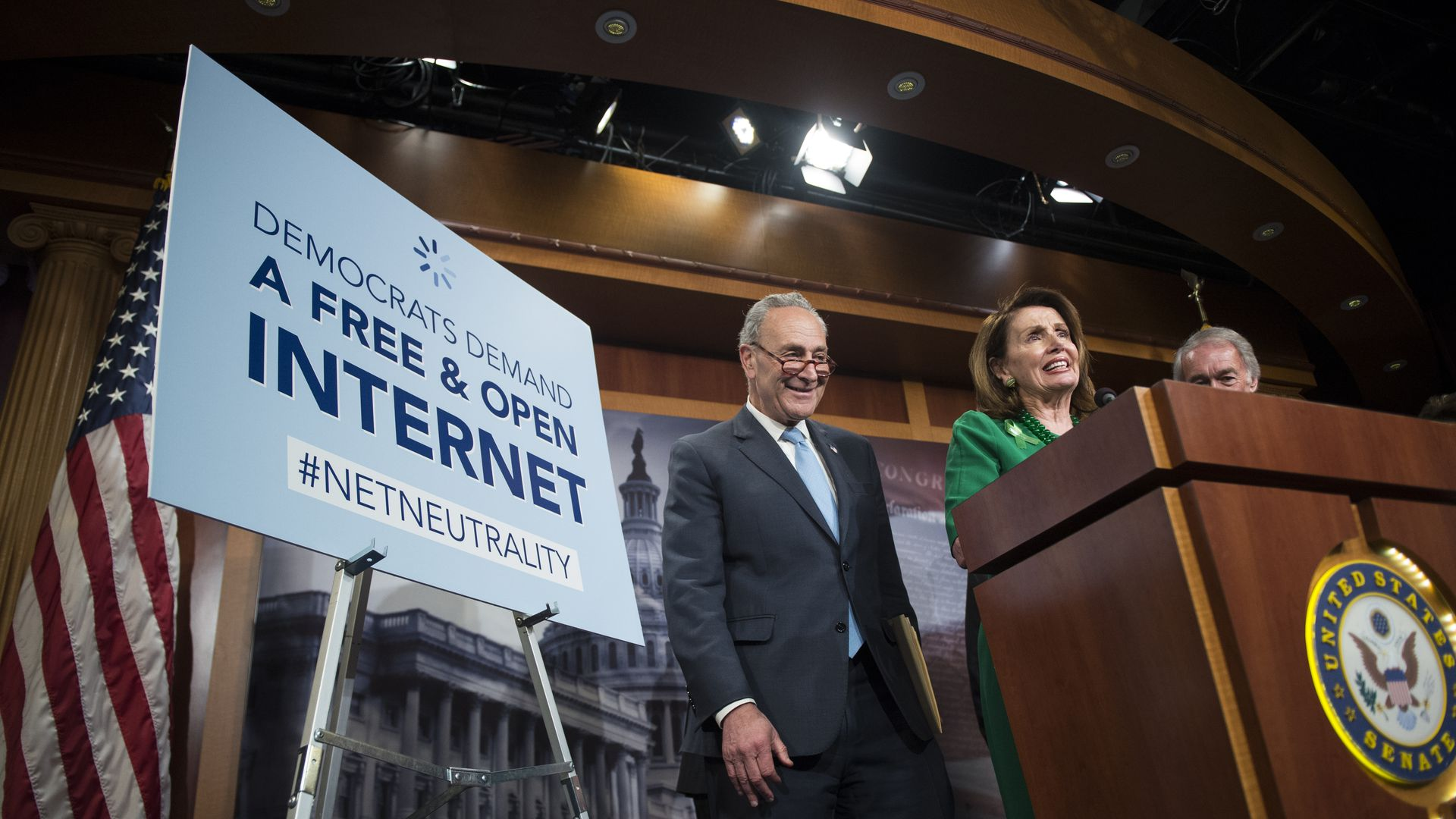 Two people stand next to a pro-net neutrality sign