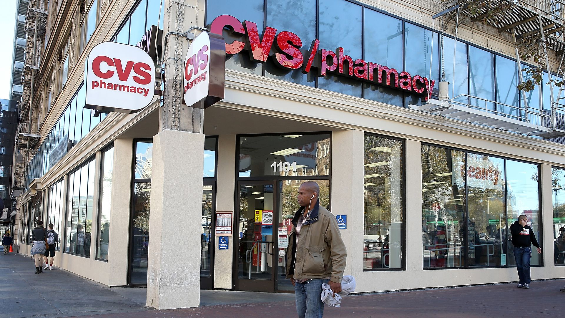 A man walks outside a CVS pharmacy building.