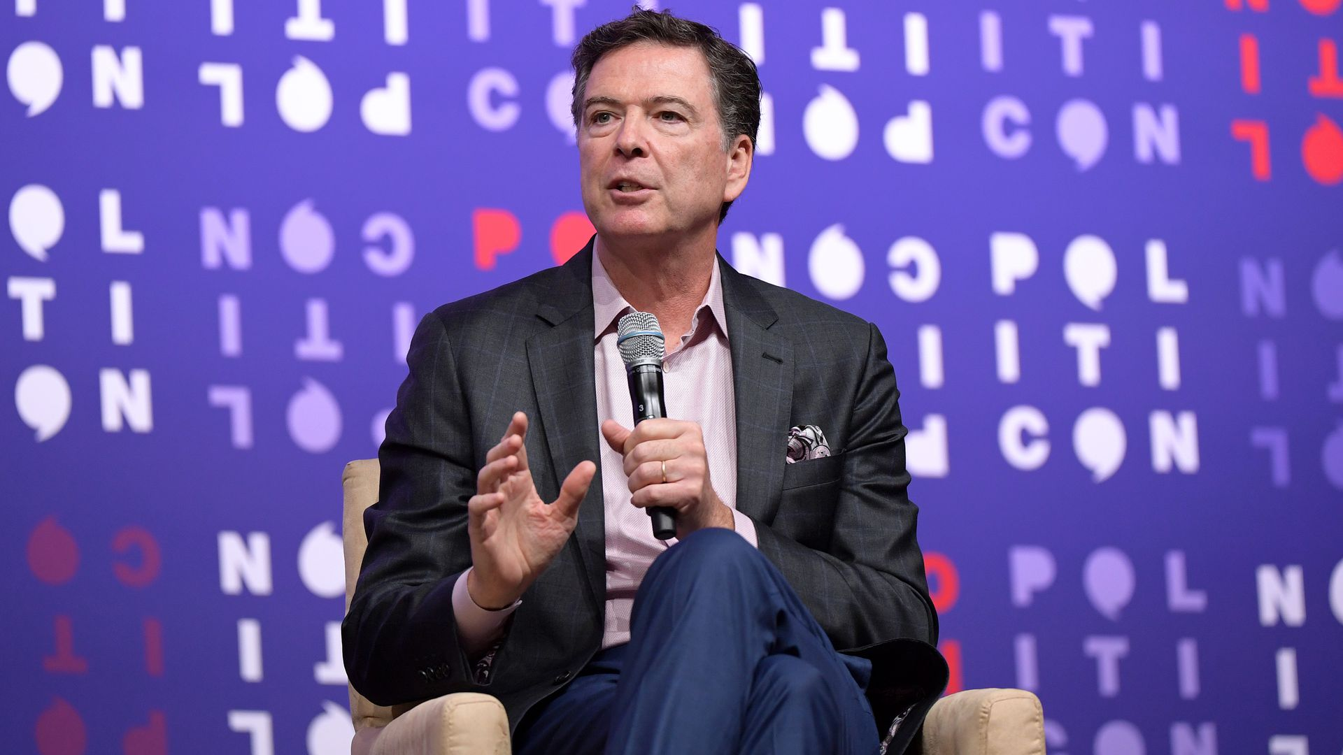 Former FBI Director James Comey sits in a chair and speaks into a mic as he is interviewed.