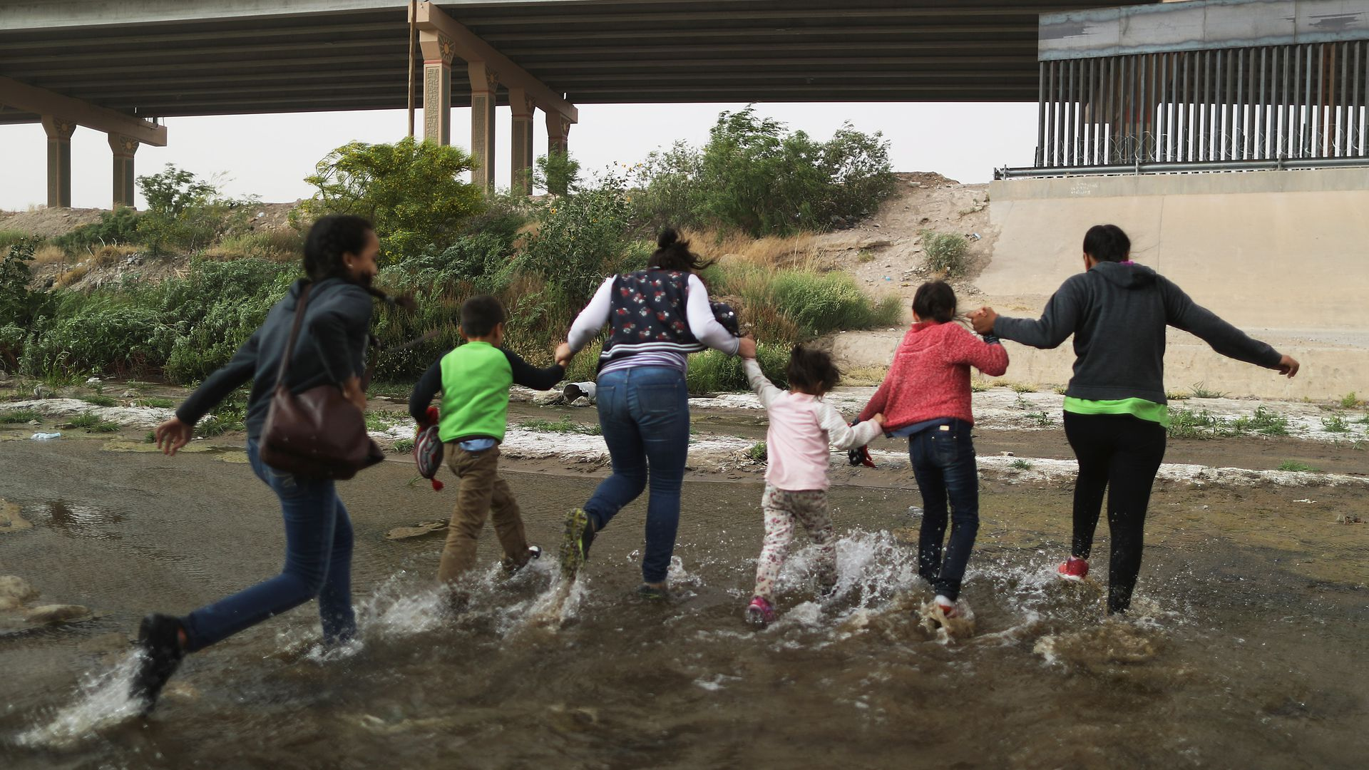 A group of 5 migrant women and young girls run through a puddle toward the U.S. border.