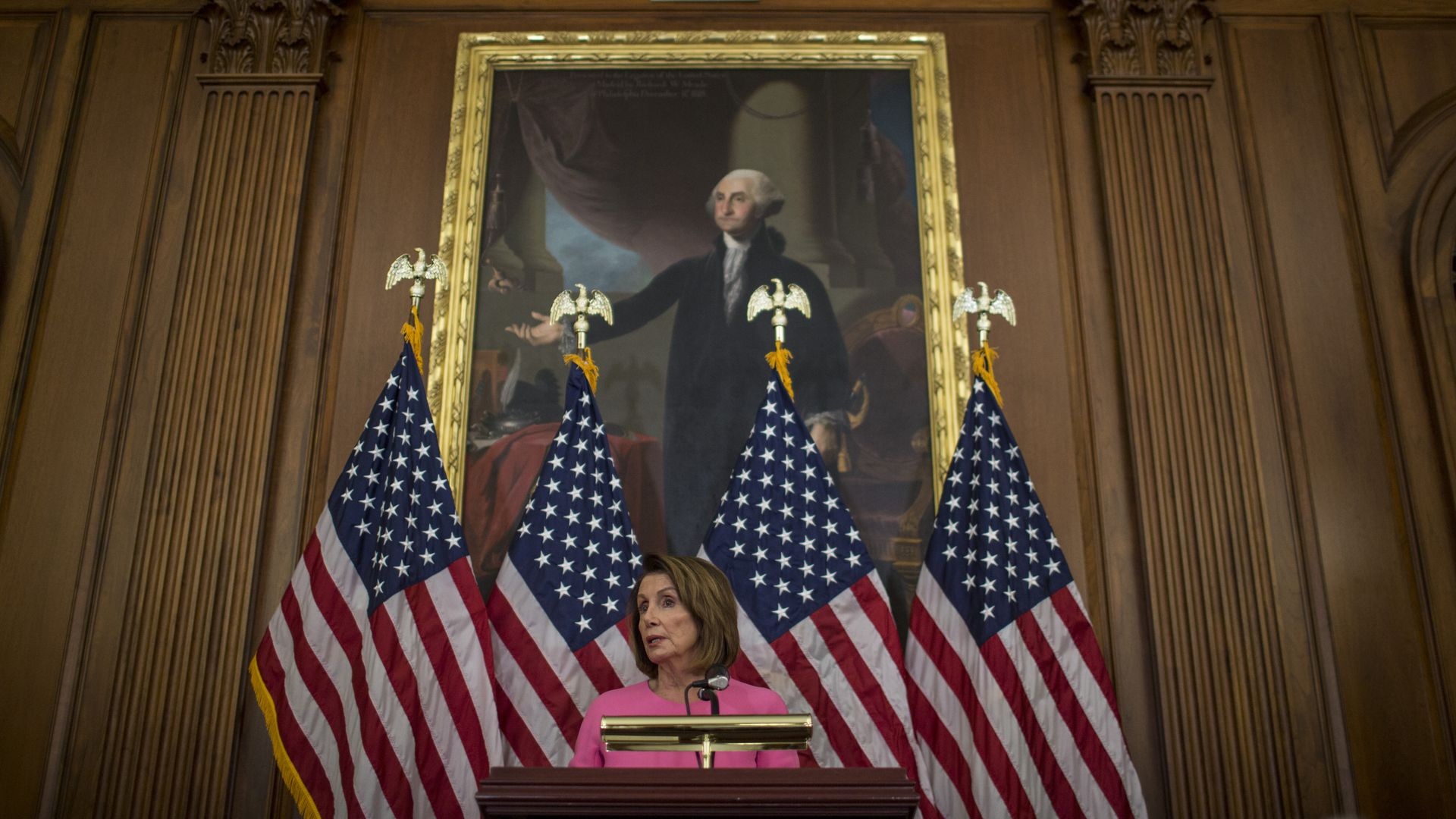 Nancy Pelosi standing in front of a portrait of George Washington