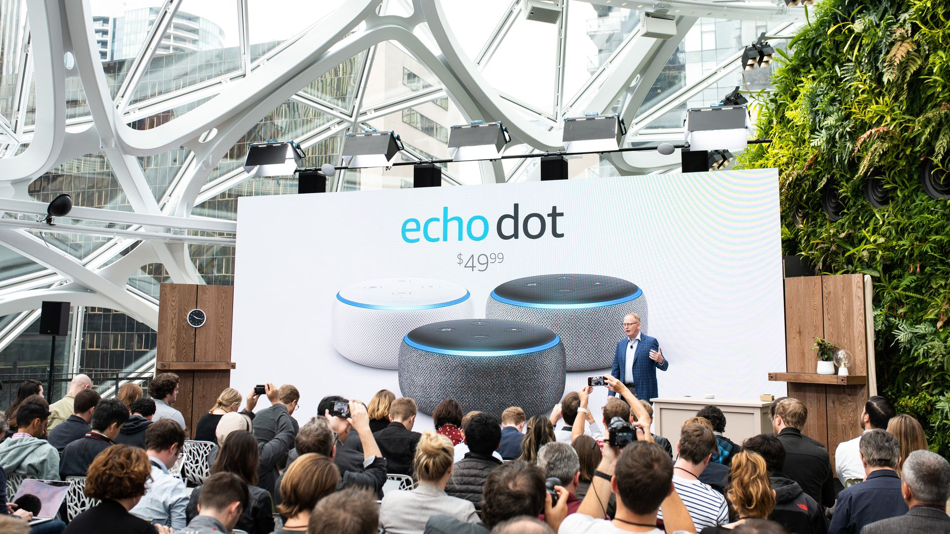 In this image, a crowd surrounds a stage that supports a large Amazon Echo Dot advertisement.