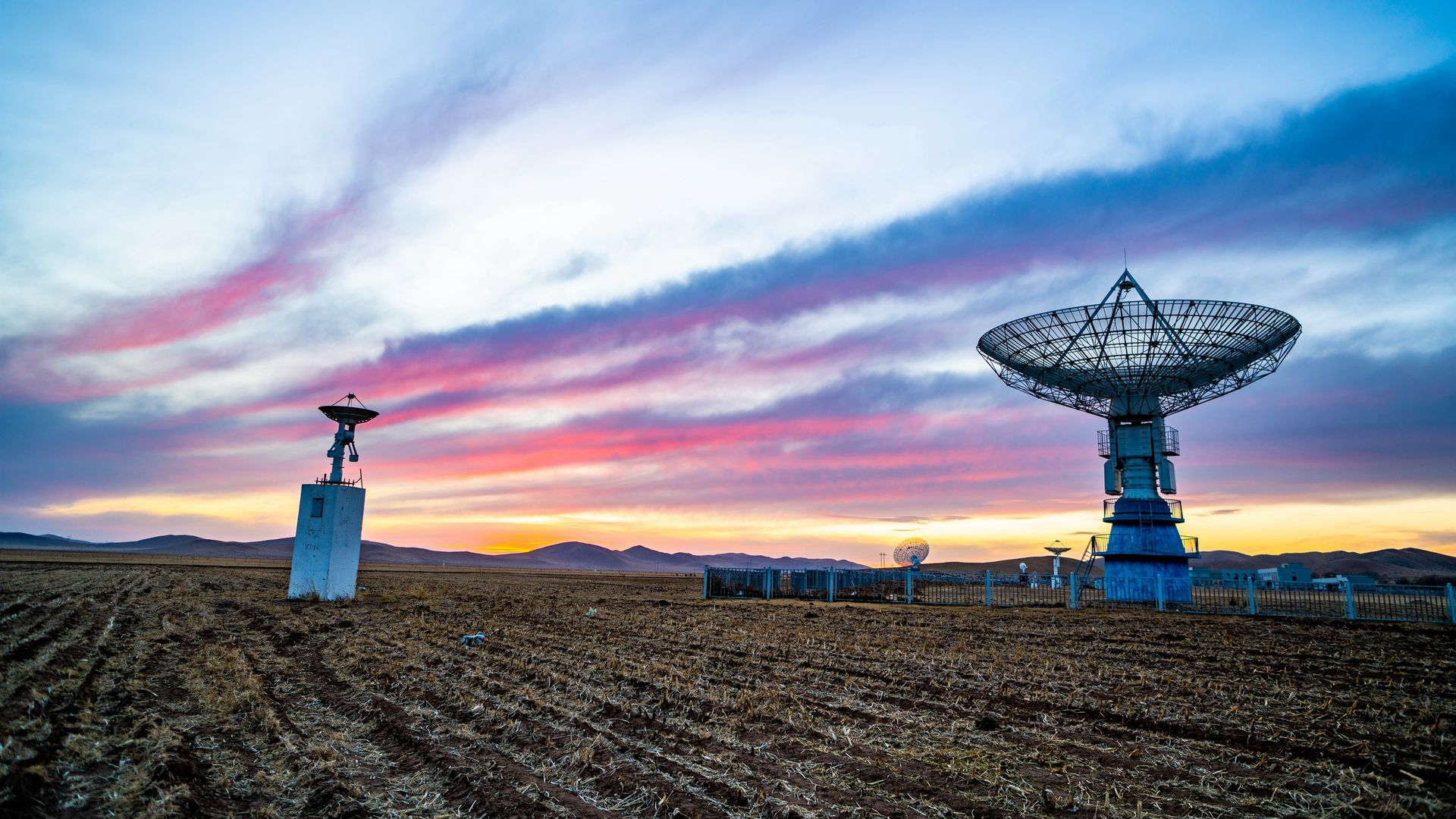 Chinese solar observatory equipment in a field in front of a beautiful sunset or sunrise.