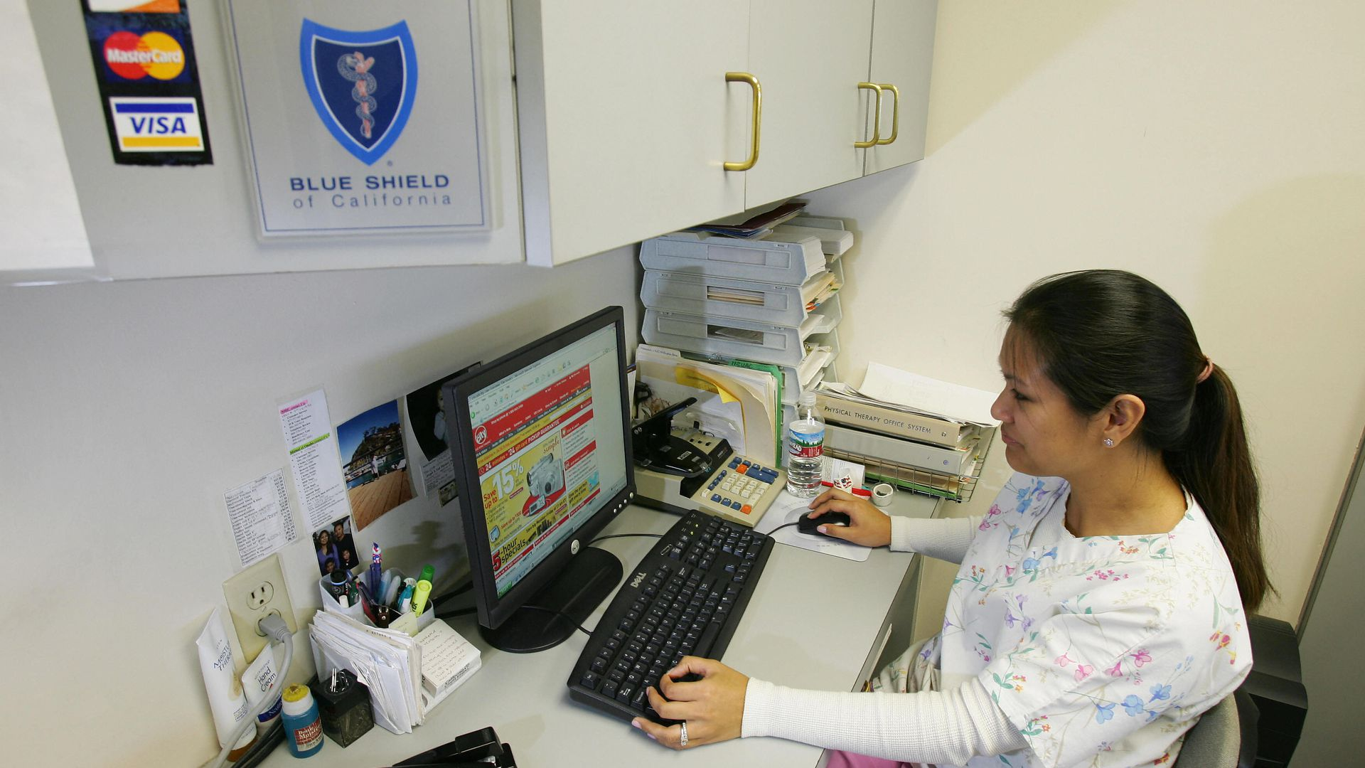 A medical billing specialist sits at her computer