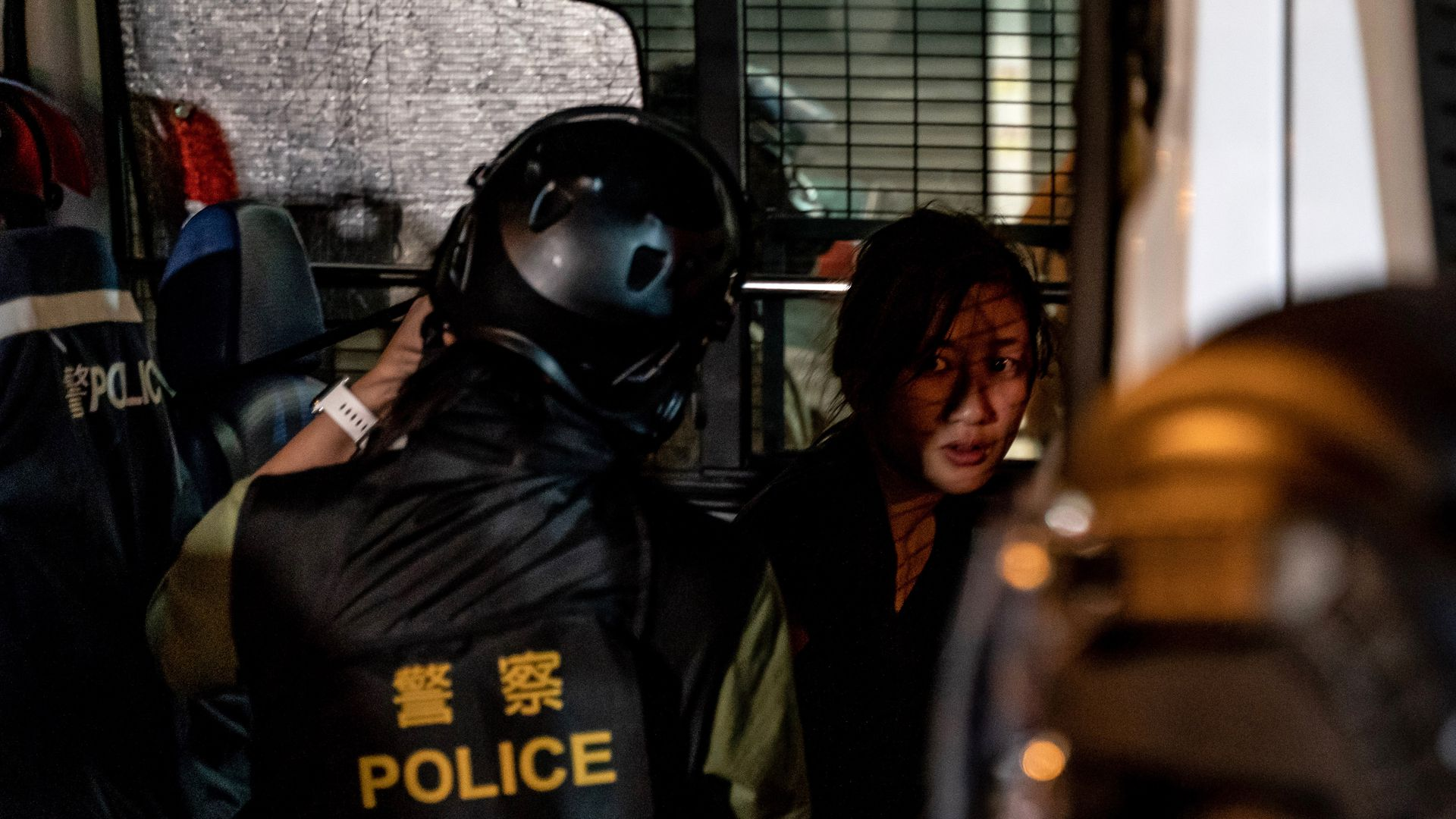 A pro-democracy protester being detained by riot police.