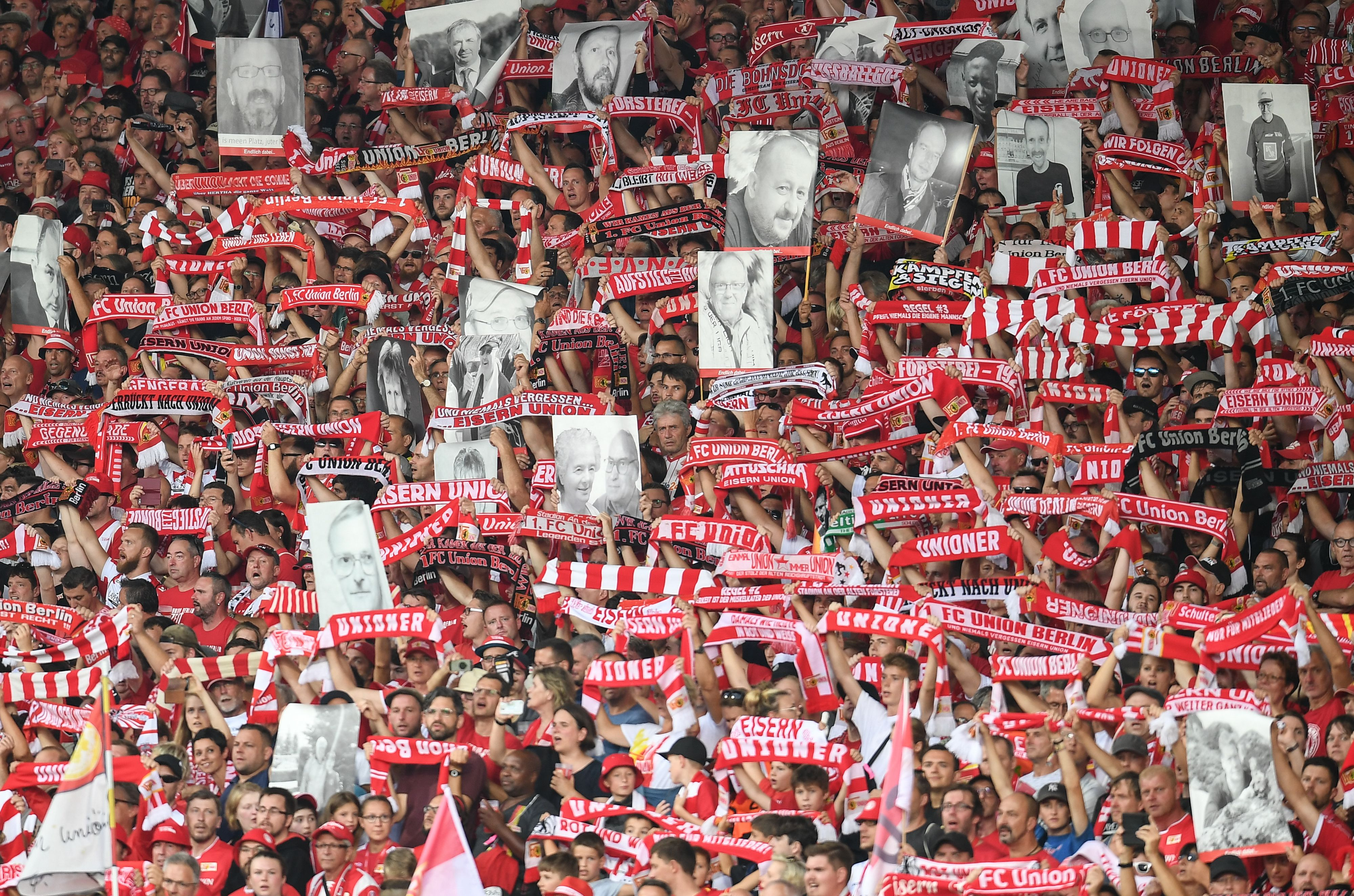 Union Berlin fans hold up photos of deceased supporters