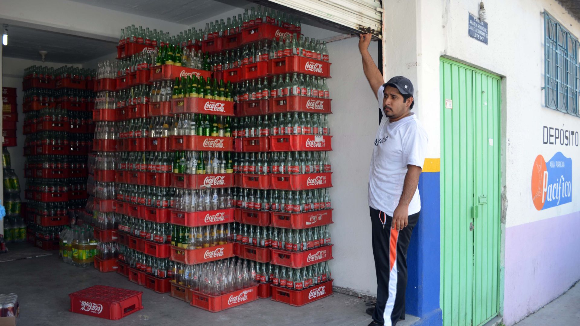 An man at a beverage deposit with cases of mostly empty Coke bottles in Mexico