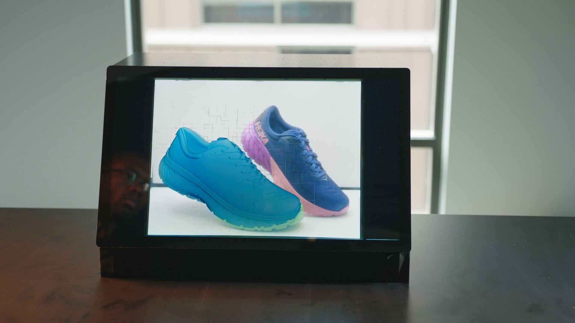 A digital shoe appears on the left side of Adobe's transparent display prototype, with a real sneaker in a light box in the background.