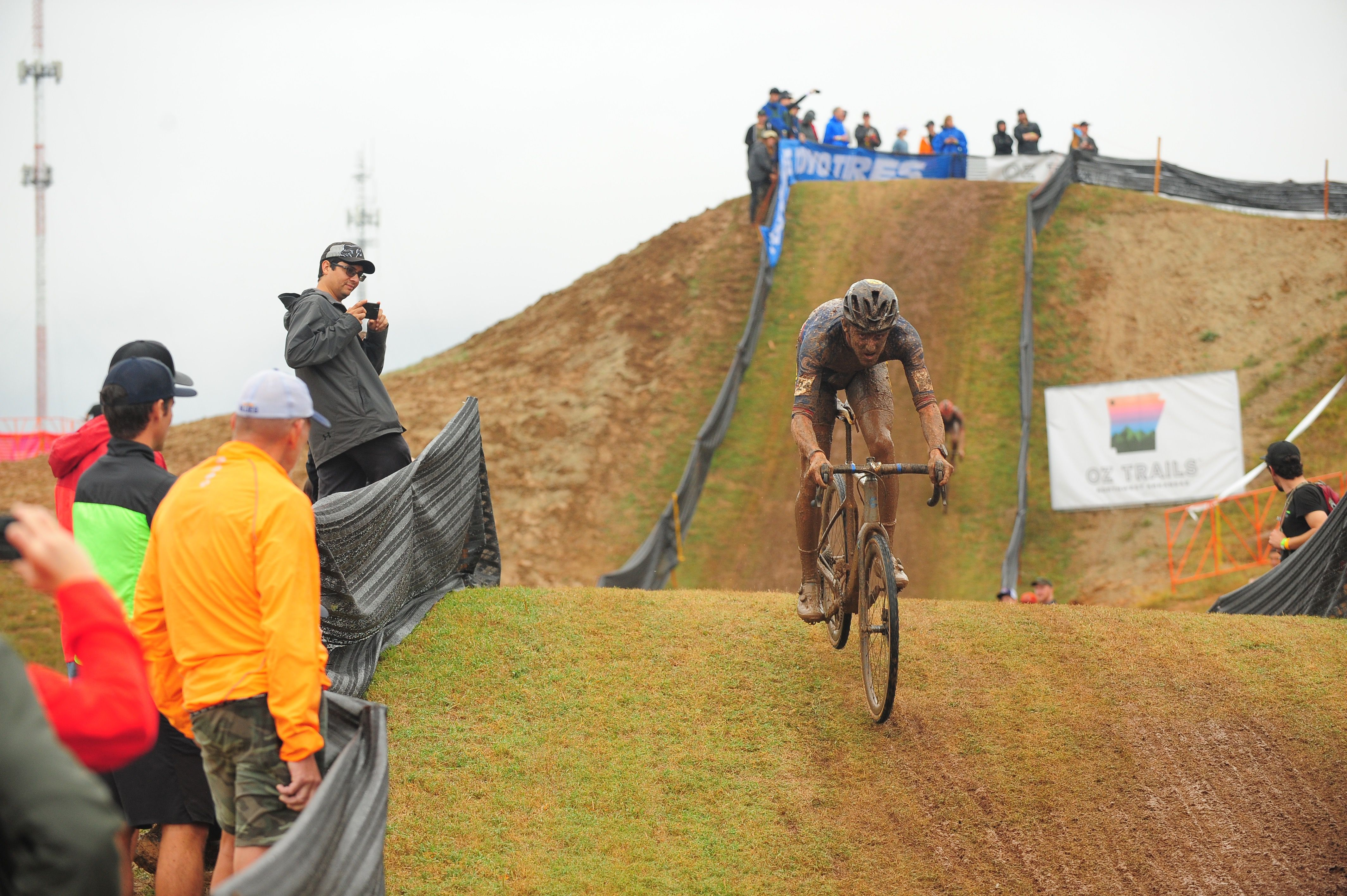 Photo of a muddy man coming down a hill on a bike.